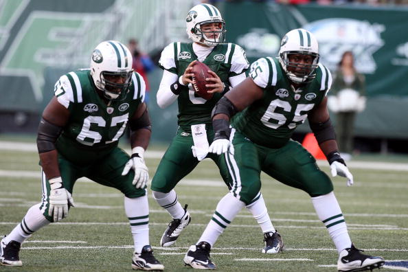 EAST RUTHERFORD, NJ - NOVEMBER 29:  Mark Sanchez #6 of the New York Jets looks to throw a pass against the Carolina Panthers as Damien Woody #67 and Brandon Moore #65 defend on November 29, 2009 at Giants Stadium in East Rutherford, New Jersey.  (Photo by
