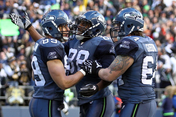 SEATTLE, WA - JANUARY 08:  John Carlson #89 of the Seattle Seahawks celebrates his 11-yard first quarter touchdown reception with teammates Cameron Morrah #88 and Mike Gibson #64 against the New Orleans Saints during the 2011 NFC wild-card playoff game at