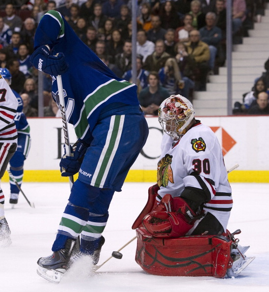 VANCOUVER, CANADA - FEBRUARY 4: Goalie Marty Turco #30 of the Chicago Blackhawks makes a pad save while Ryan Kesler #17 of the Vancouver Canucks tries to screen and redirect the puck during the second period in NHL action on February 04, 2011 at Rogers Ar