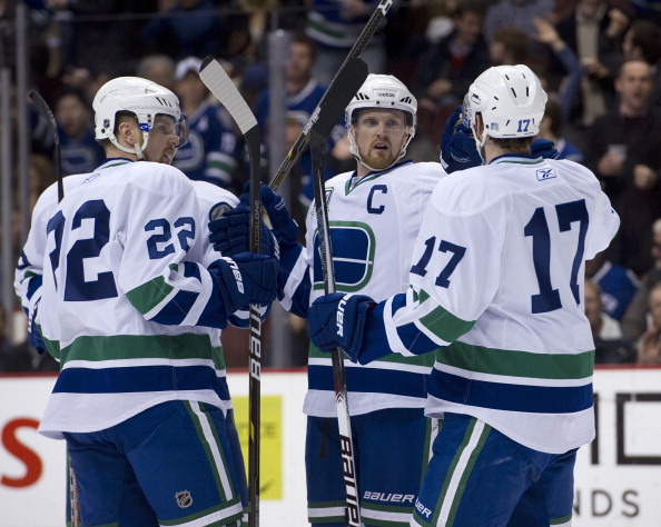 VANCOUVER, CANADA - FEBRUARY 22: Henrik Sedin #33 celebrates with Daniel Sedin #22 and Ryan Kesler #17 of the Vancouver Canucks after scoring a power play goal against the Montreal Canadiens during the second period in NHL action on February 22, 2011 at R
