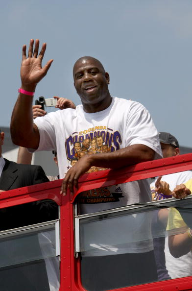 LOS ANGELES, CA - JUNE 17:  Los Angeles Lakers Hall of Fame player and team executive Magic Johnson waves to the crowd from the top of a double decker bus at the start of Los Angeles Lakers NBA championship victory parade outside the Staples Center on Jun