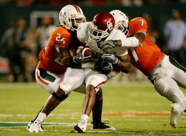 MIAMI GARDENS, FL - OCTOBER 3:  DeMarco Murray #7 of the Oklahoma Sooners gets tackled by Ray Ray Armstrong #26 and Vaughn Telemaque #7  of the Miami Hurricanes after getting first down in the second quarter of the game on October 3, 2009 at Landshark Sta