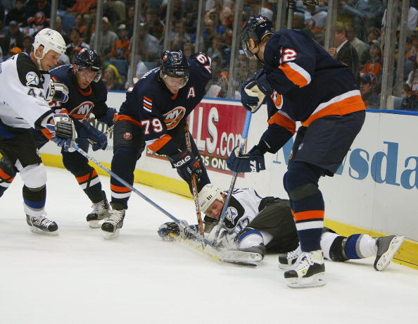UNIONDALE, NY - APRIL 14:  Alexei Yashin #79 and Oleg Kvasha #12 of the New York Islanders dig for the puck as Ruslan Fedotenko #17 of the Tampa Bay Lightning scrambles to cover the puck during game four of the Eastern Conference Quarterfinals of the 2004