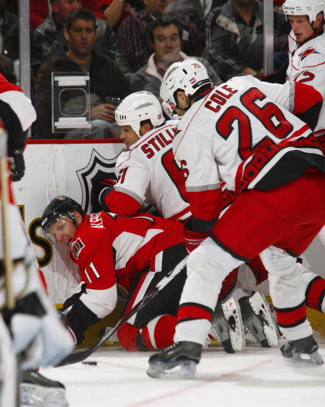 OTTAWA, CANADA- OCTOBER 11:  Daniel Alfredsson #11 of the Ottawa Senators is knocked to the ice by the combined efforts of Cory Stillman #61;Erik Cole #26 and Eric Staal #12 of the Carolina Hurricanes during first period action of a game on October 11, 20
