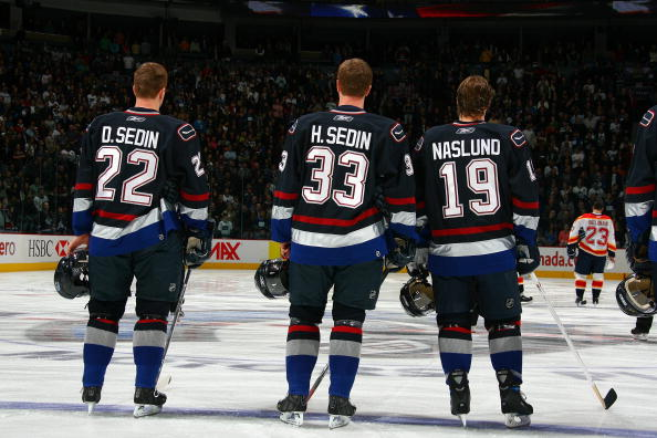 VANCOUVER, BC - JANUARY 7:  Daniel Sedin #22, Henrik Sedin #33 and Markus Naslund #19 of the Vancouver Canucks stand for the National Anthem before the game against the Florida Panthers at General Motors Place on January 7, 2007 in Vancouver, British Colu
