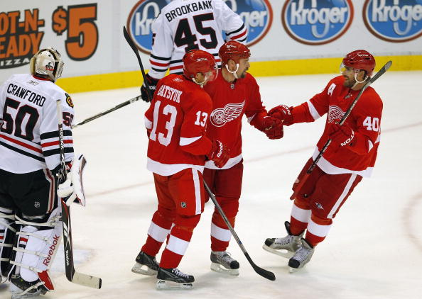 DETROIT - SEPTEMBER 24: Tomas Holmstrom #96 of the Detroit Red Wings celebrates a first period goal with Pavel Datsyuk and Henrik Zetterberg #40 during a pre season game on September 24, 2010 at Joe Louis Arena in Detroit, Michigan.  (Photo by Gregory Sha