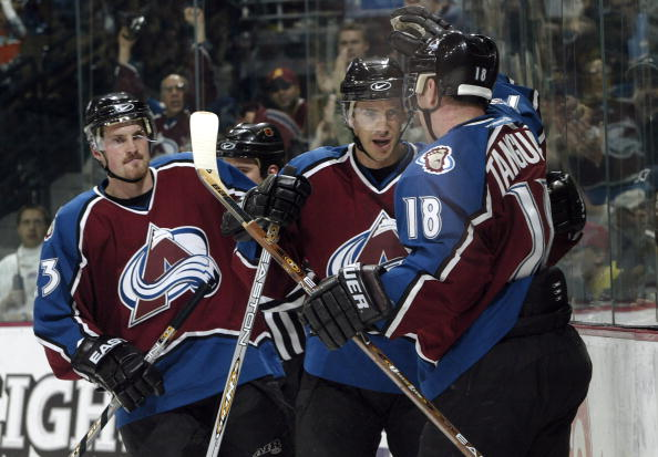 DENVER - NOVEMBER 20:  Joe Sakic #19 and Alex Tanguay #18 of the Colorado Avalanche celebrate after combining for a power play goal against the New York Rangers in the first period November 20, 2003 at the Pepsi Center in Denver, Colorado.  Milan Hejduk #
