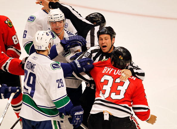 CHICAGO - MARCH 05: Referees try to break up a first period fight between Dustin Byfuglien #33 of the Chicago Blackhawks and Alexander Burrows #14 of the Vancouver Canucks at the United Center on March 5, 2010 in Chicago, Illinois. The Blackhawks defeated