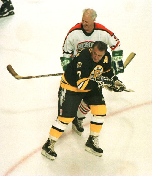 19 Jan 1996:  Wielding a double bladed stick, Gordie Howe #9 of the NHL Heroes checks Phil Esposito #7 of the Boston Bruins Heroes from behind during the second period of the NHL Heroes of Hockey game played at the Fleet Center in Boston, Massachusetts. M