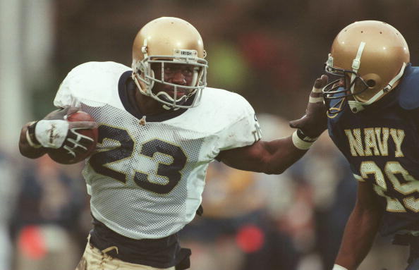 2 Nov 1996:  Running back Autry Denson (left) of the University of Notre Dame straight-arms defensive back Sean Andrews of Navy during the Fighting Irish 54-27 Shamrock Classic win over Navy in Dublin, Ireland. Mandatory Credit: Billy Stickland/ALLSPORT