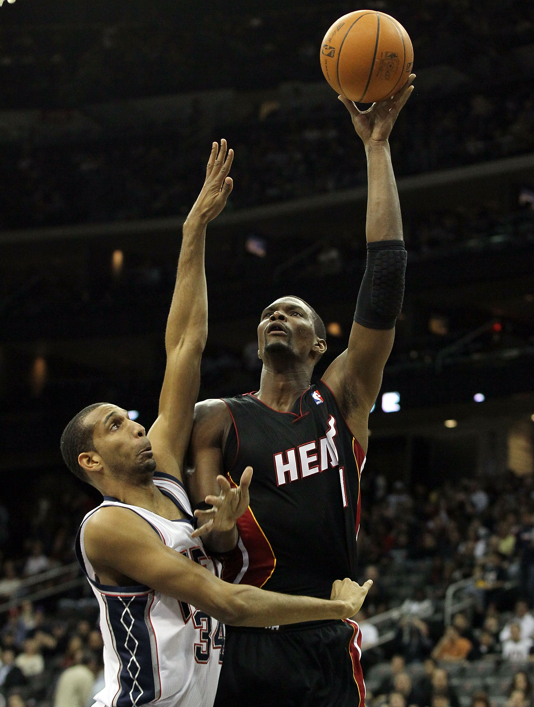 NEWARK, NJ - APRIL 03:  Chris Bosh #1 of the Miami Heat pits up a basket against Brandan Wright #34 of the New Jersey Nets at the Prudential Center on April 3, 2011 in Newark, New Jersey.NOTE TO USER: User expressly acknowledges and agrees that, by downlo