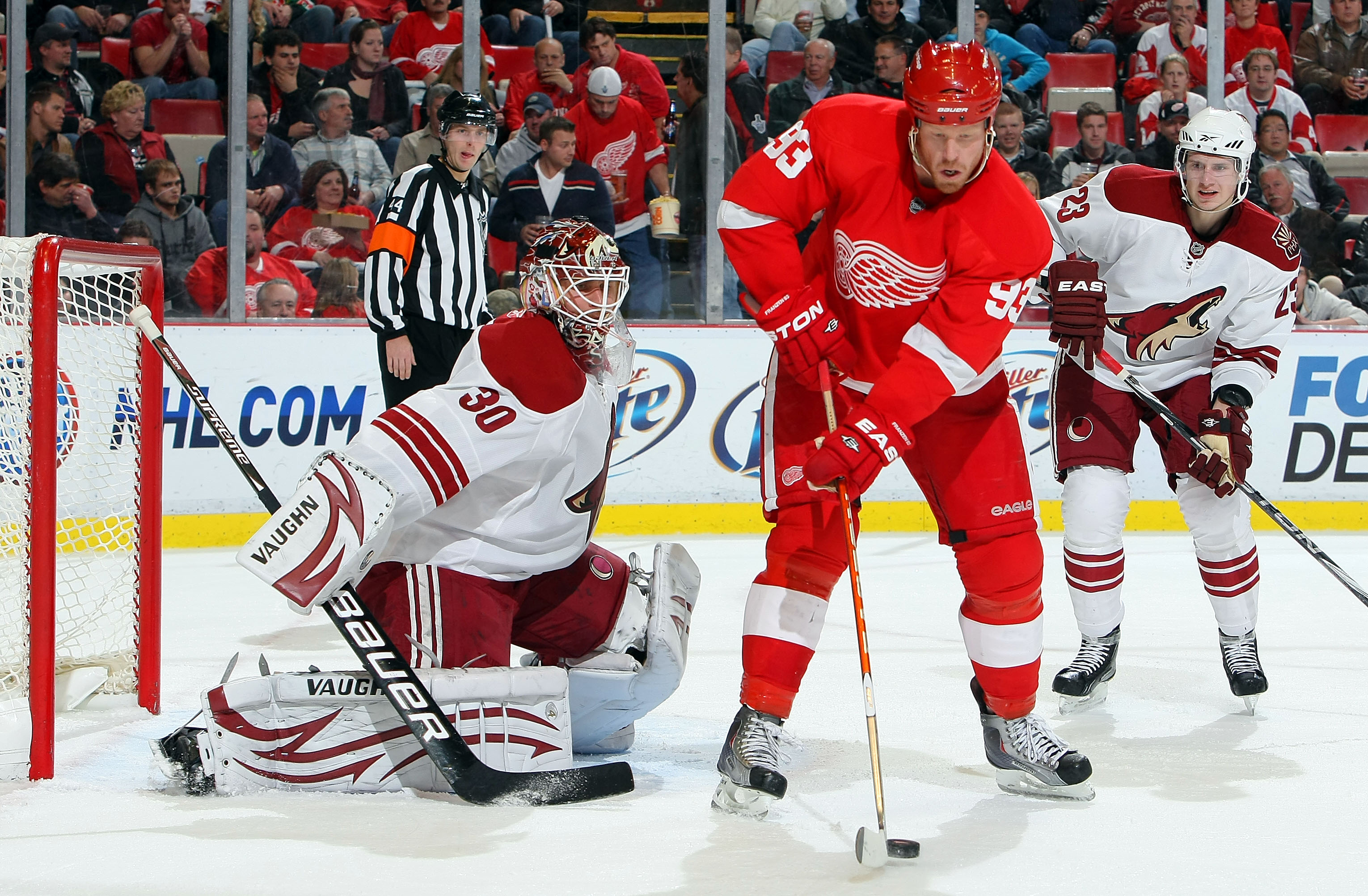 DETROIT - OCTOBER 28:  Oliver Ekman-Larsson #23 of the Phoenix Coyotes looks on as Johan Franzen #93 of the Detroit Red Wings tips a shot past for a goal against Ilya Bryzgalov #30 of the Phoenix Coyotes during their NHL game at Joe Louis Arena on October