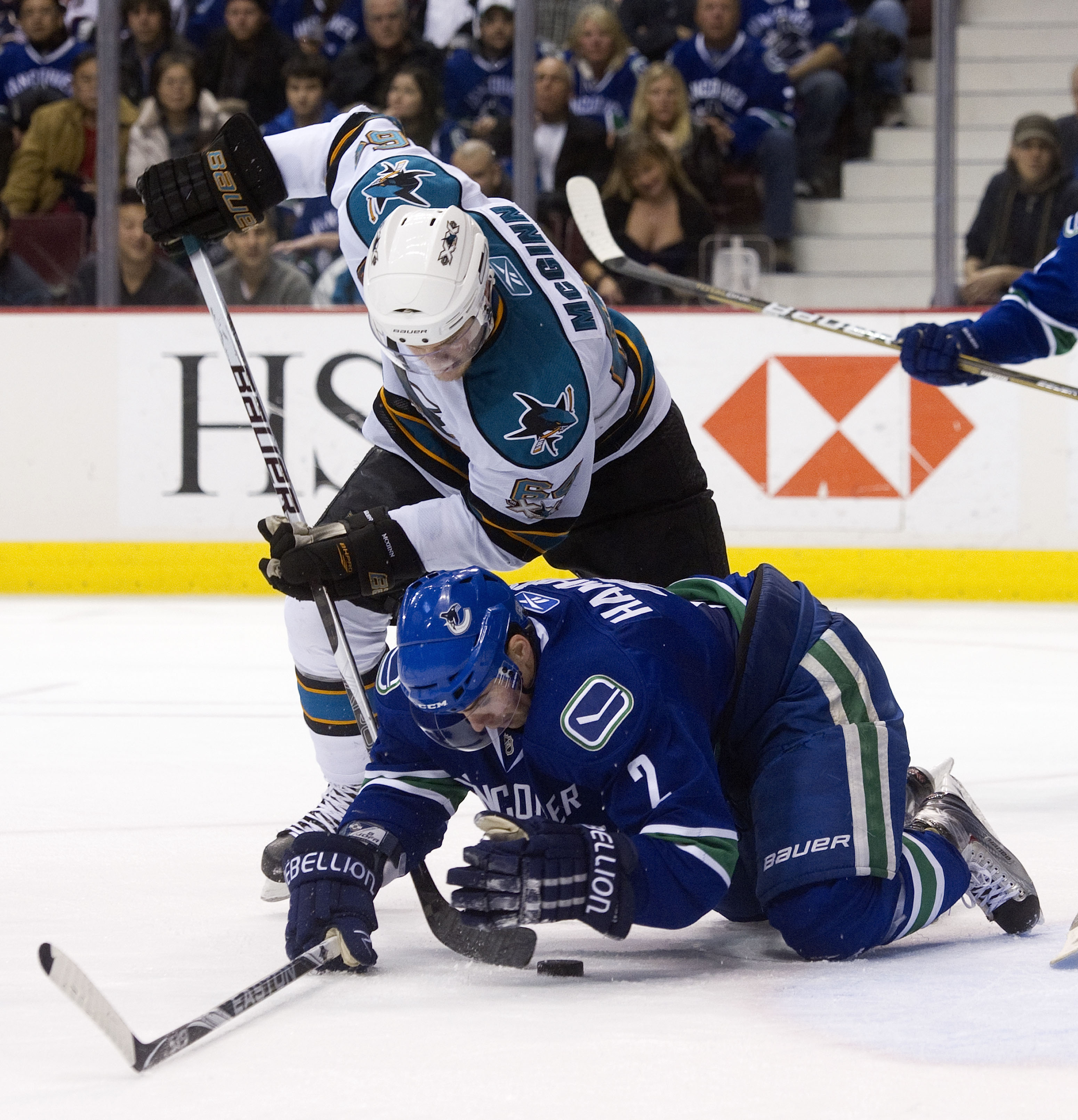 VANCOUVER, CANADA - JANUARY 20: Dan Hamhuis #2 of the Vancouver Canucks tries to cover up the puck during a scramble while Jamie McGinn #64 of the San Jose Sharks tries to dig it loose during the third period in NHL action on January 20, 2011 at Rogers Ar