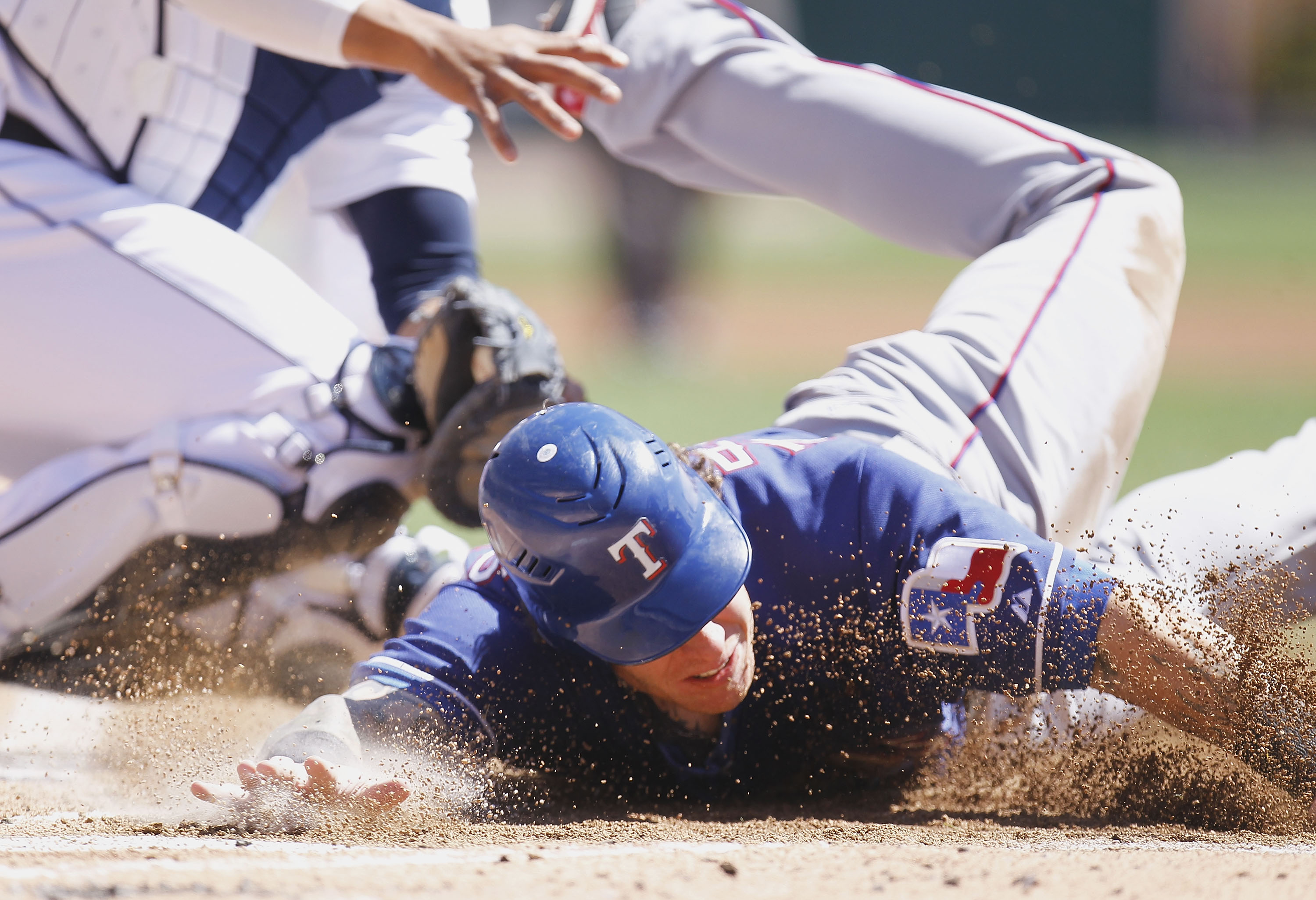 DETROIT, MI - APRIL 12:  Josh Hamilton #32 of the Texas Rangers slides into home plate during the third inning while playing the Detroit Tigers at Comerica Park on April 12, 2011 in Detroit, Michigan. Hamilton was out from a tag by Victor Martinez  (Photo