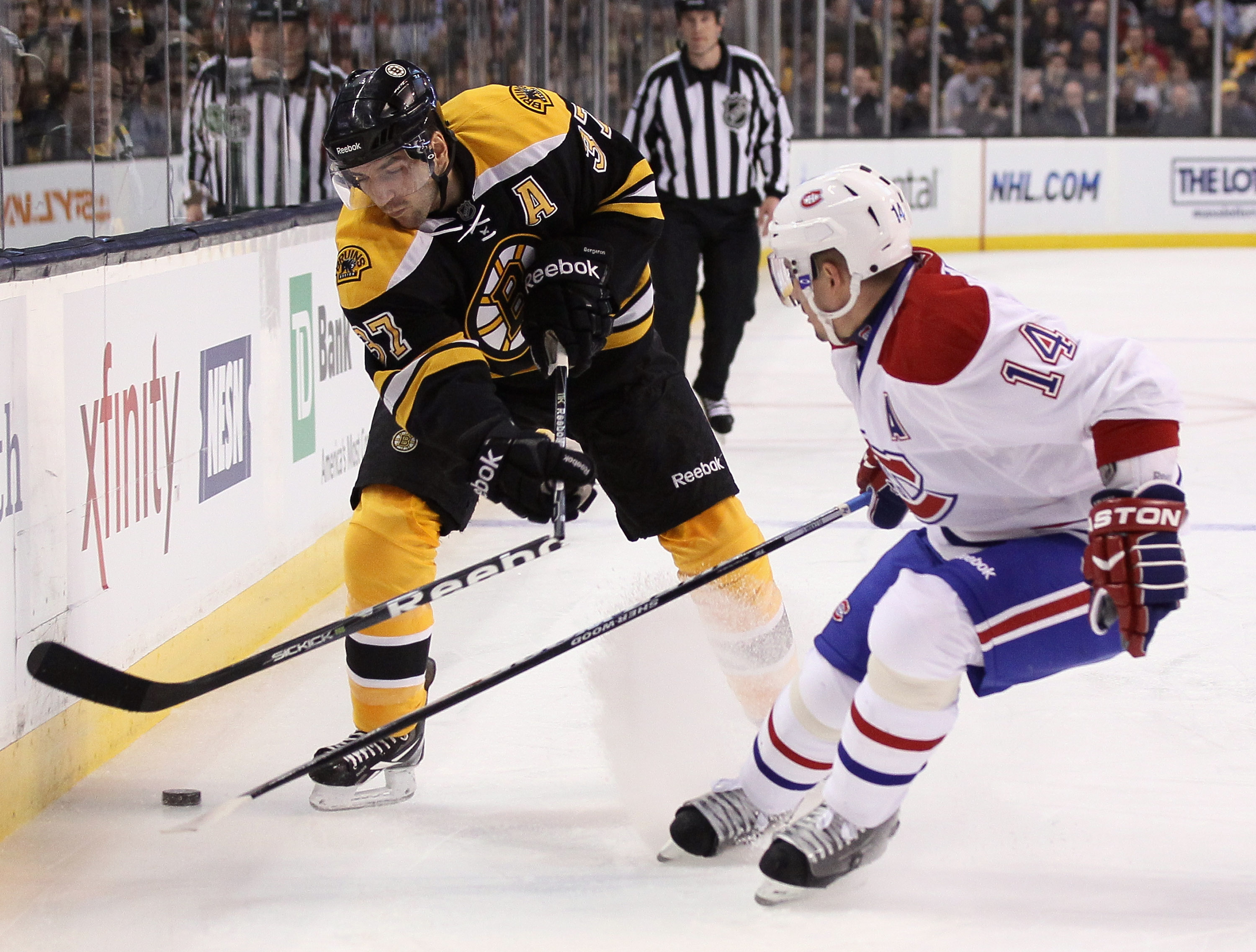 BOSTON, MA - MARCH 24:  Patrice Bergeron #37 of the Boston Bruins breaks his stick as he takes a shot while Tomas Plekanec #14 of the Montreal Canadiens defends on March 24, 2011 at the TD Garden in Boston, Massachusetts.  (Photo by Elsa/Getty Images)