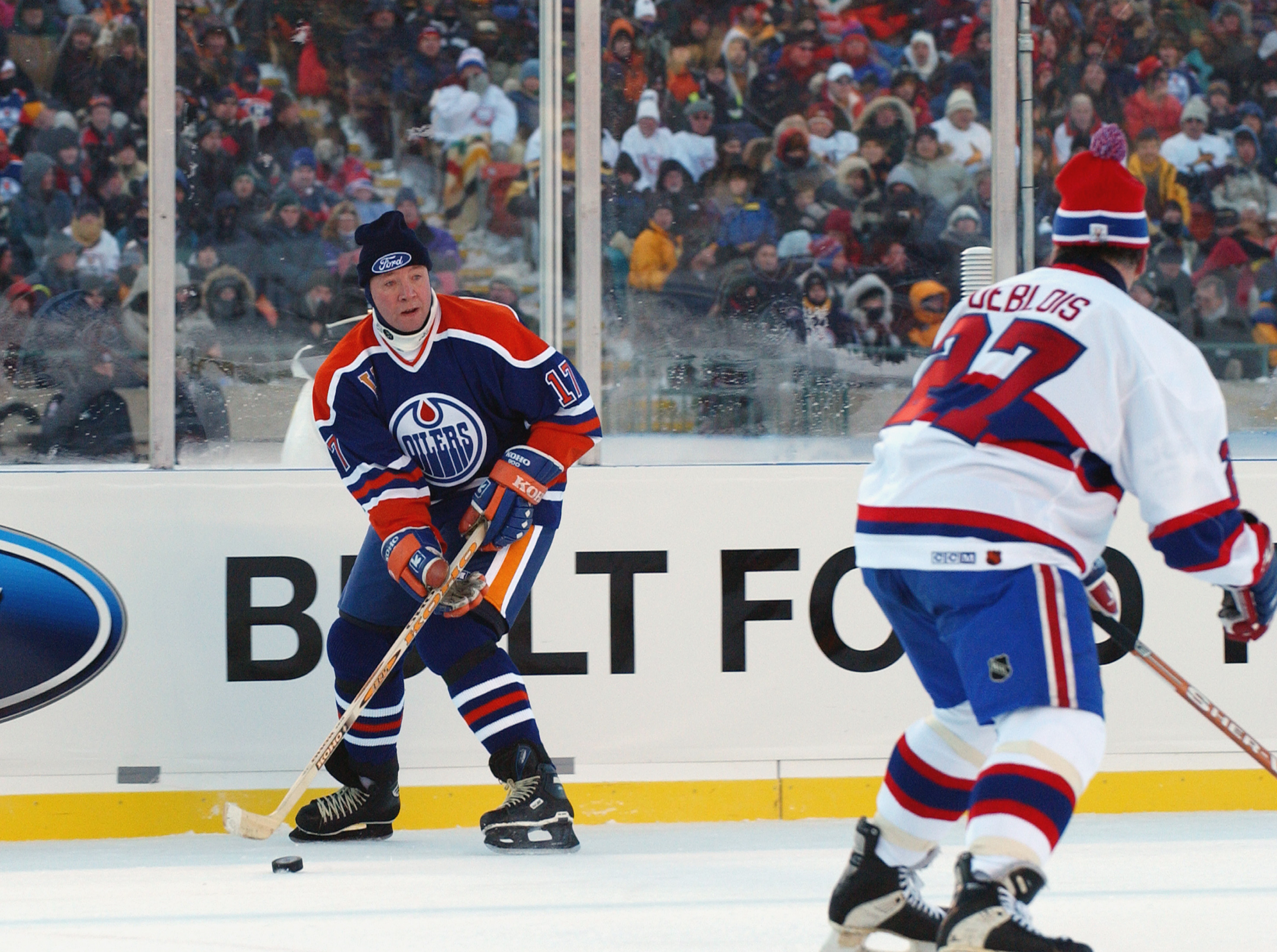 EDMONTON, CANADA - NOVEMBER 22:  Jari Kurri #17 of the Edmonton Oilers looks to make a play against Lucen Deblois #27 of the Montreal Canadiens during the Molson Canadien Heritage Classic on November 22, 2003 at Commonwealth Stadium in Edmonton, Canada. T