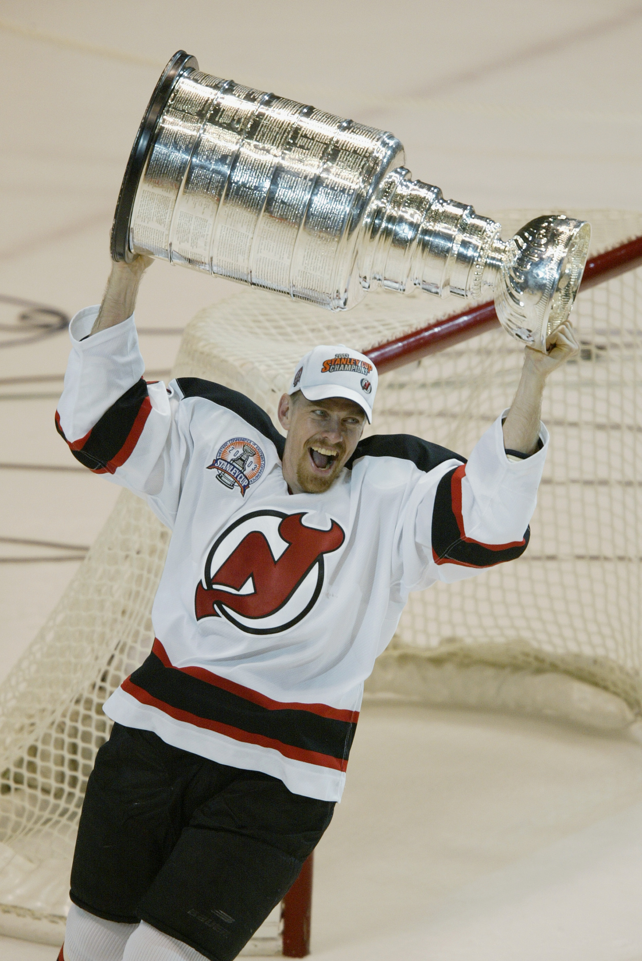 EAST RUTHERFORD, NJ - JUNE 9:   Joe Nieuwendyk #25 of the New Jersey Devils raises the Stanley Cup after defeating the Mighty Ducks of Anaheim in game seven of the 2003 Stanley Cup Finals at Continental Airlines Arena on June 9, 2003 in East Rutherford, N
