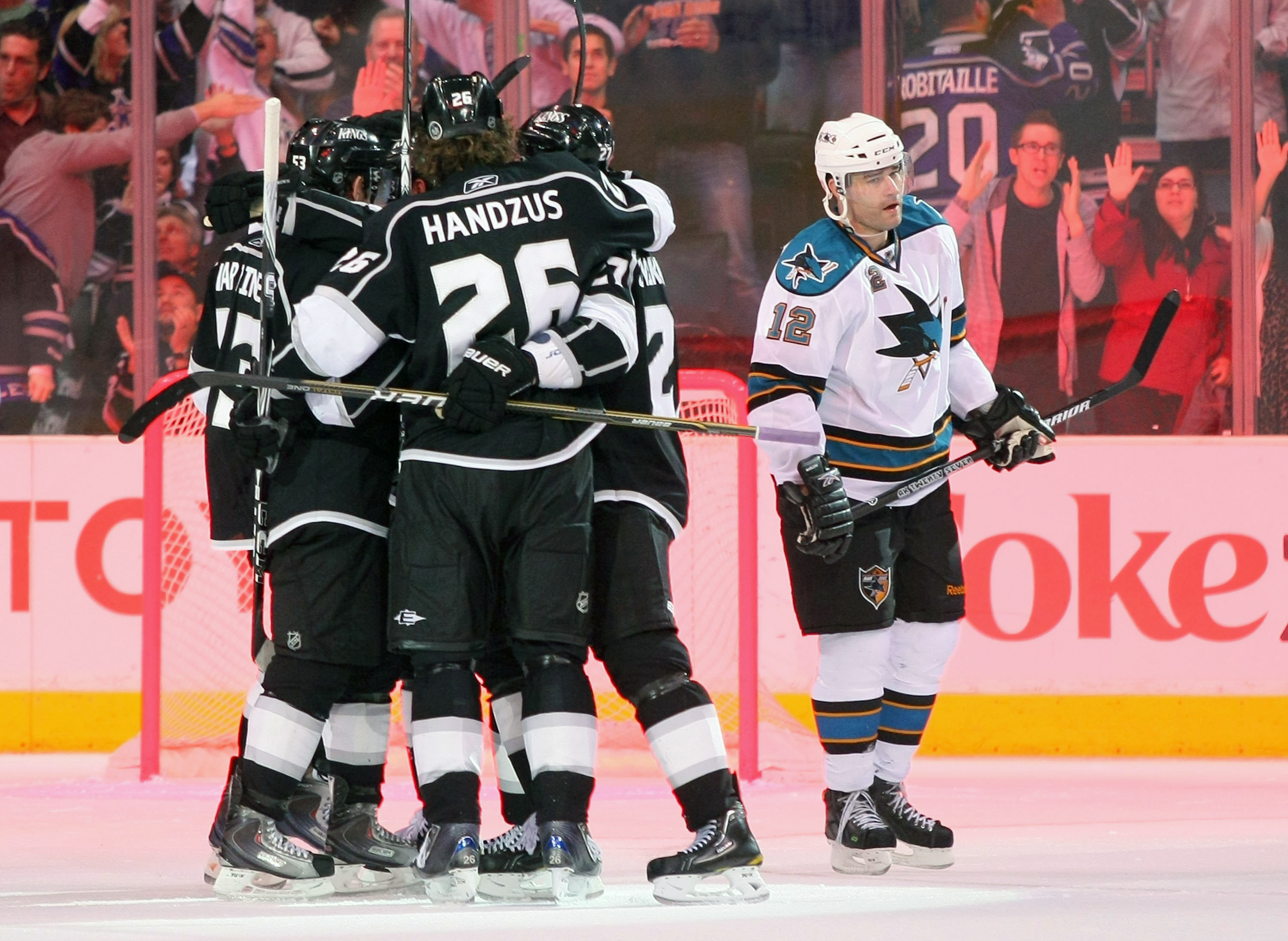 LOS ANGELES, CA - MARCH 24:  Alec Martinez #53, Michal Handzus #26, Dustin Brown #23 and Alexei Ponikarovsky #27 of the Los Angeles Kings celebrate Brown's goal in the third period as Patrick Marleau #12 of the San Jose Sharks skates to the bench during t