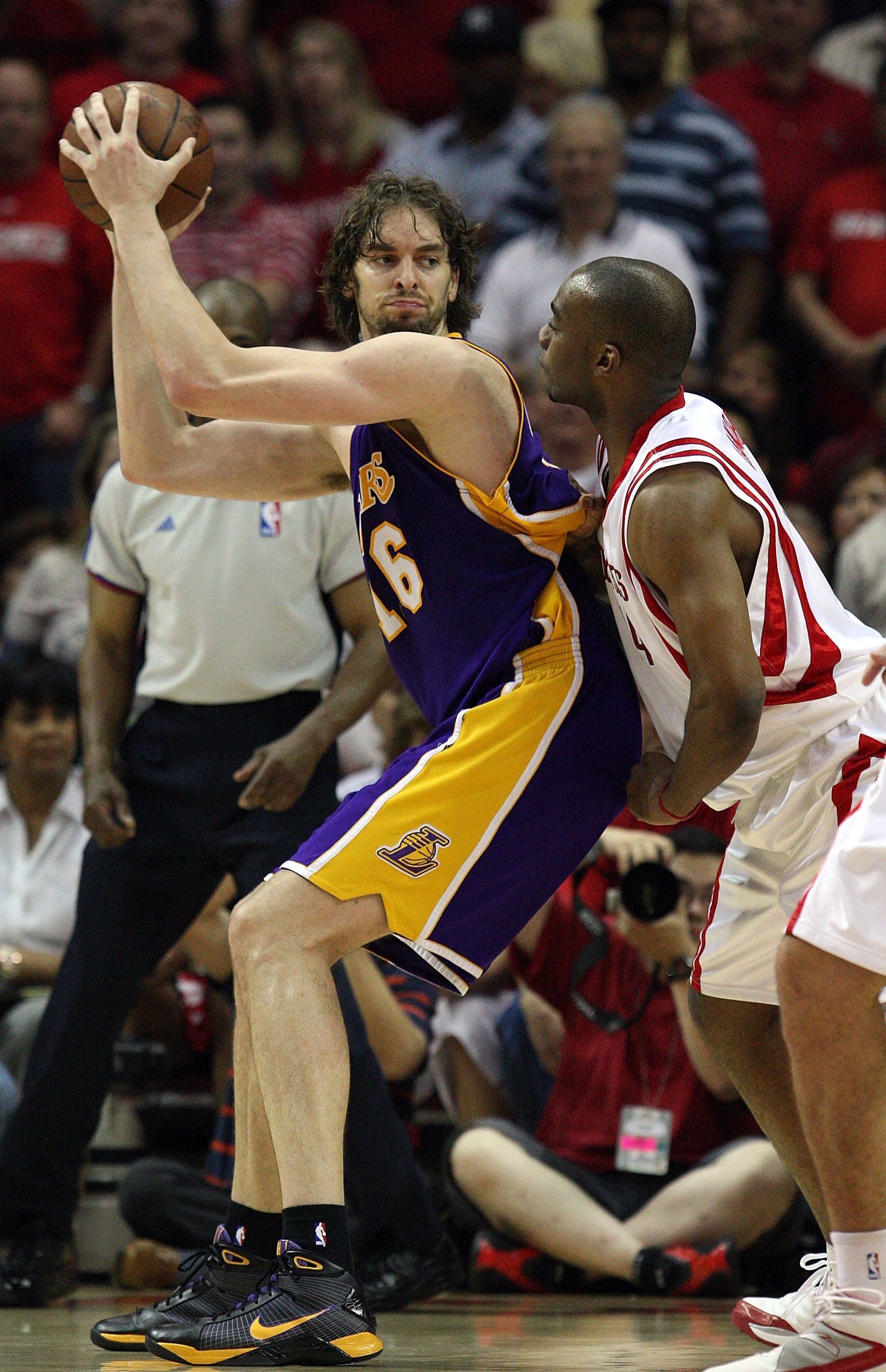 HOUSTON - MAY 14:  Center Pau Gasol #16 of the Los Angeles Lakers dribbles the ball against Carl Landry #14 of the Houston Rockets in Game Six of the Western Conference Semifinals during the 2009 NBA Playoffs at Toyota Center on May 14, 2009 in Houston, T