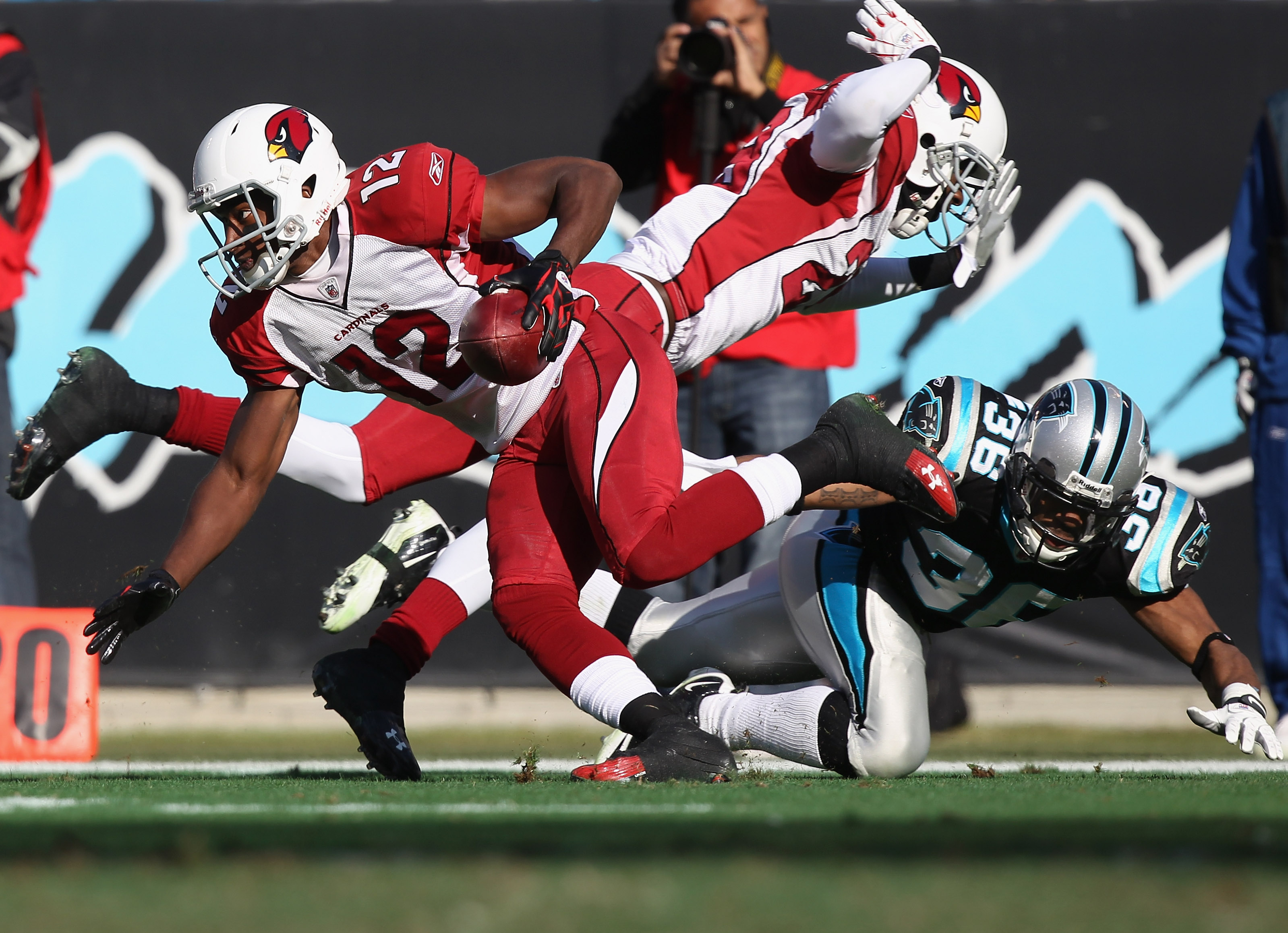 CHARLOTTE, NC - DECEMBER 19:  Dominique Rodgers-Cromartie #29 of the Arizona Cardinals hits Robert McClain #36 of the Carolina Panthers in the back as Andre Roberts #12 returns a punt during their game at Bank of America Stadium on December 19, 2010 in Ch