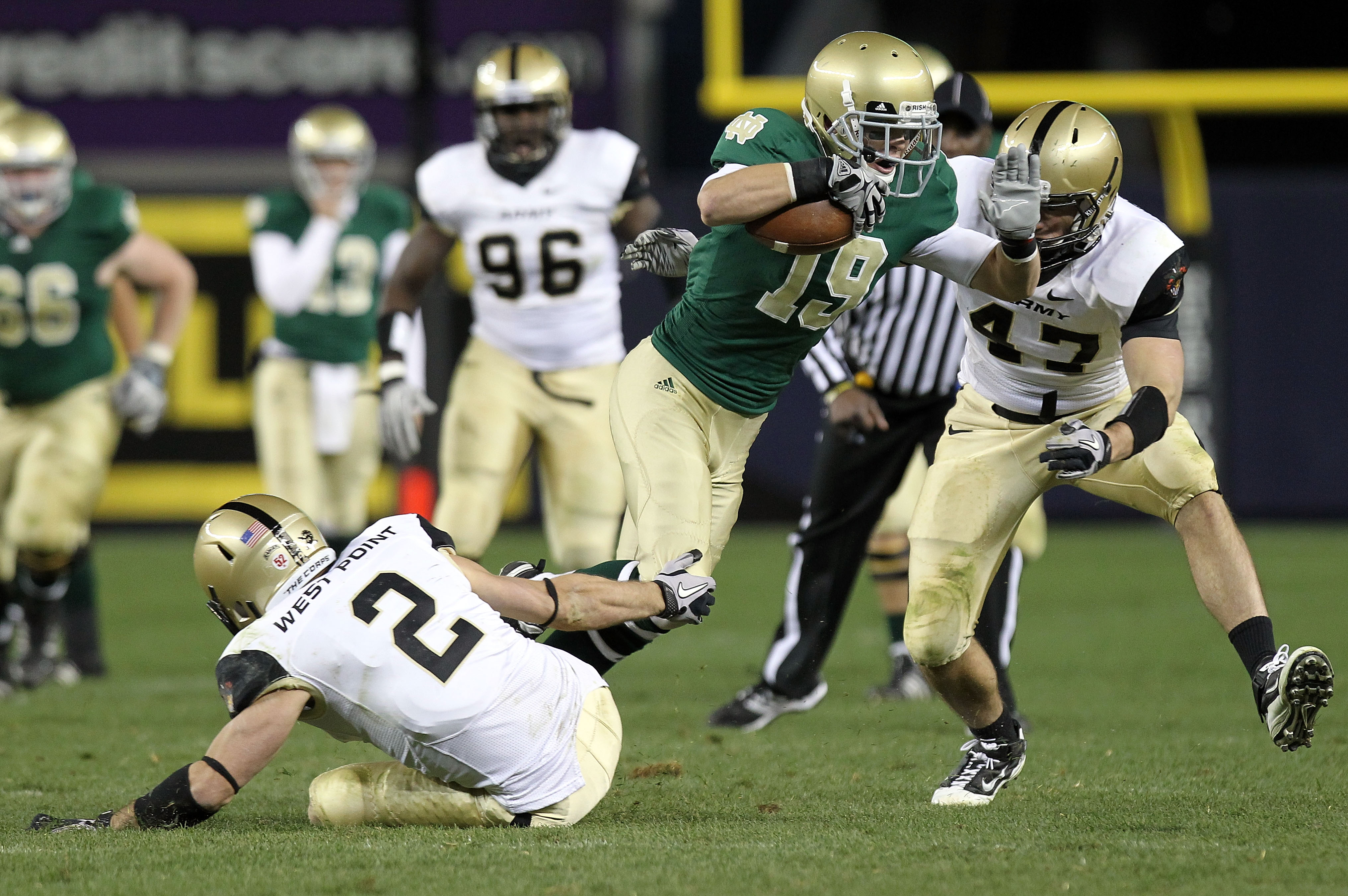 NEW YORK - NOVEMBER 20: Robby Toma #19 of the Notre Dame Fighting Irish is tackled by Richard King #2 and Bill Prosko #47 of the Army Black Knights at Yankee Stadium on November 20, 2010 in the Bronx borough of New York City.  (Photo by Nick Laham/Getty I