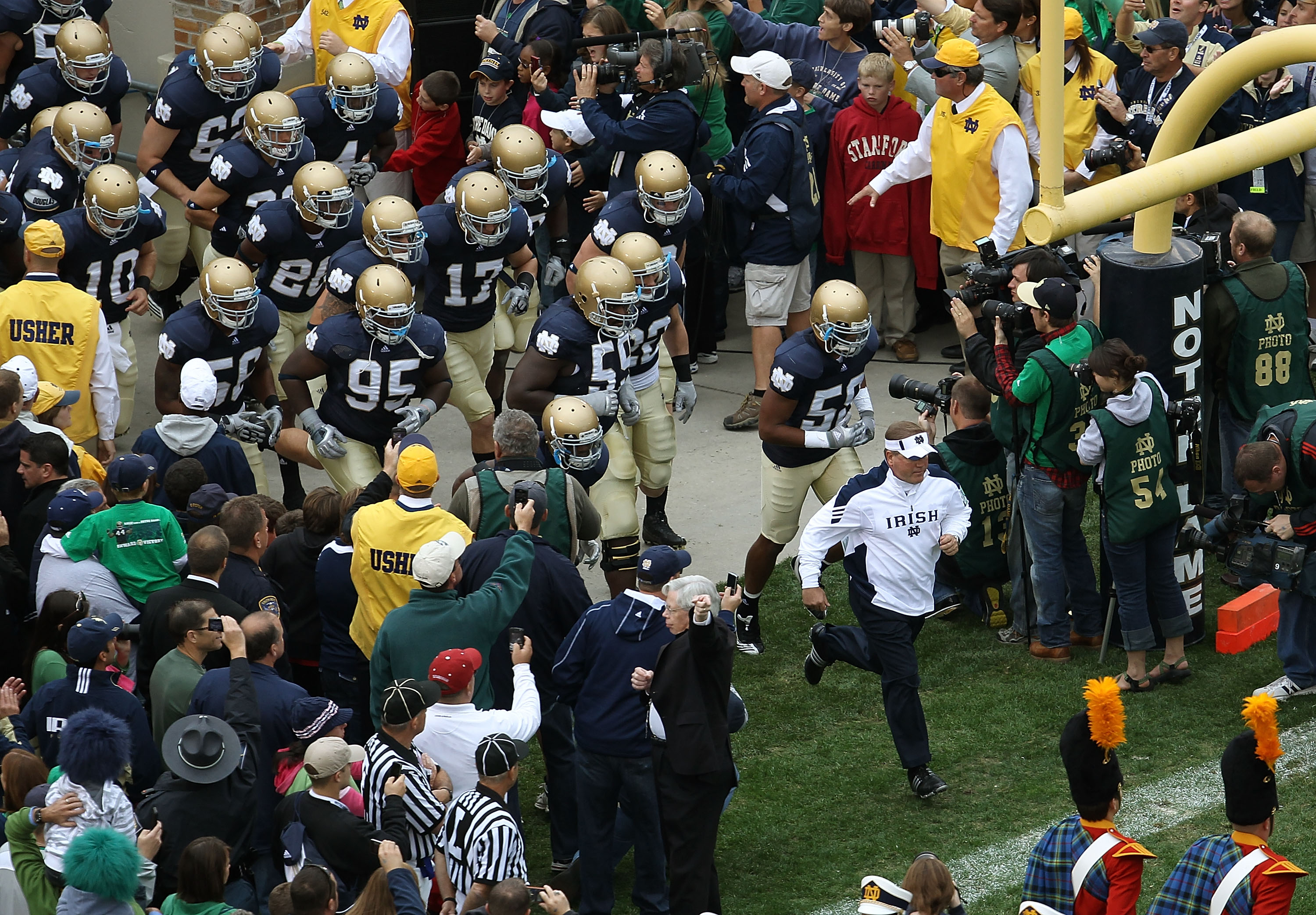 SOUTH BEND, IN - SEPTEMBER 25: Head coach Brian Kelly of the Notre Dame Fighting Irish leads his team onto the field before taking on the Stanford Cardinal at Notre Dame Stadium on September 25, 2010 in South Bend, Indiana. Stanford defeated Notre Dame 37