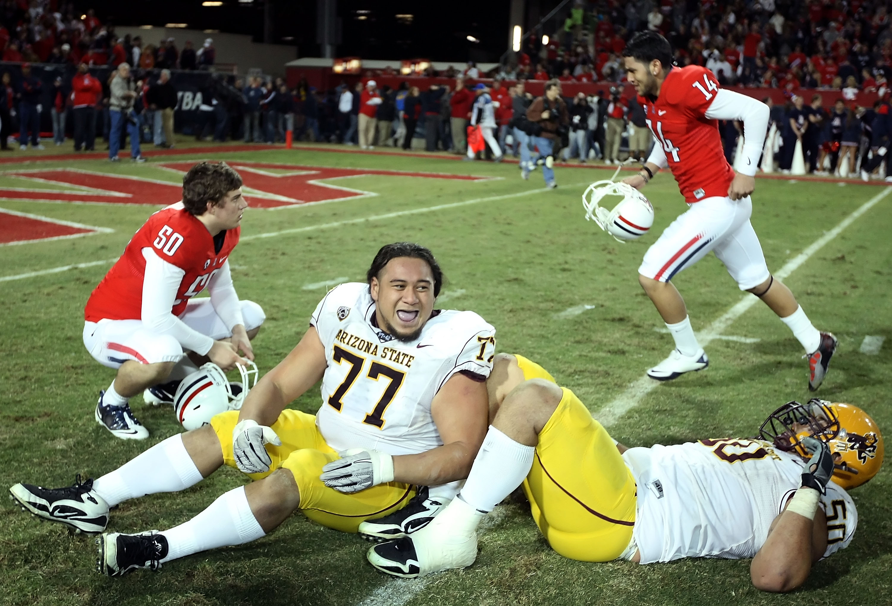 TUCSON, AZ - DECEMBER 02:  Defensive tackle Saia Falahola #77 and Lawrence Guy #50 of the Arizona State Sun Devils celebrate after defeating the Arizona Wildcats in college football game at Arizona Stadium on December 2, 2010 in Tucson, Arizona. The Sun D
