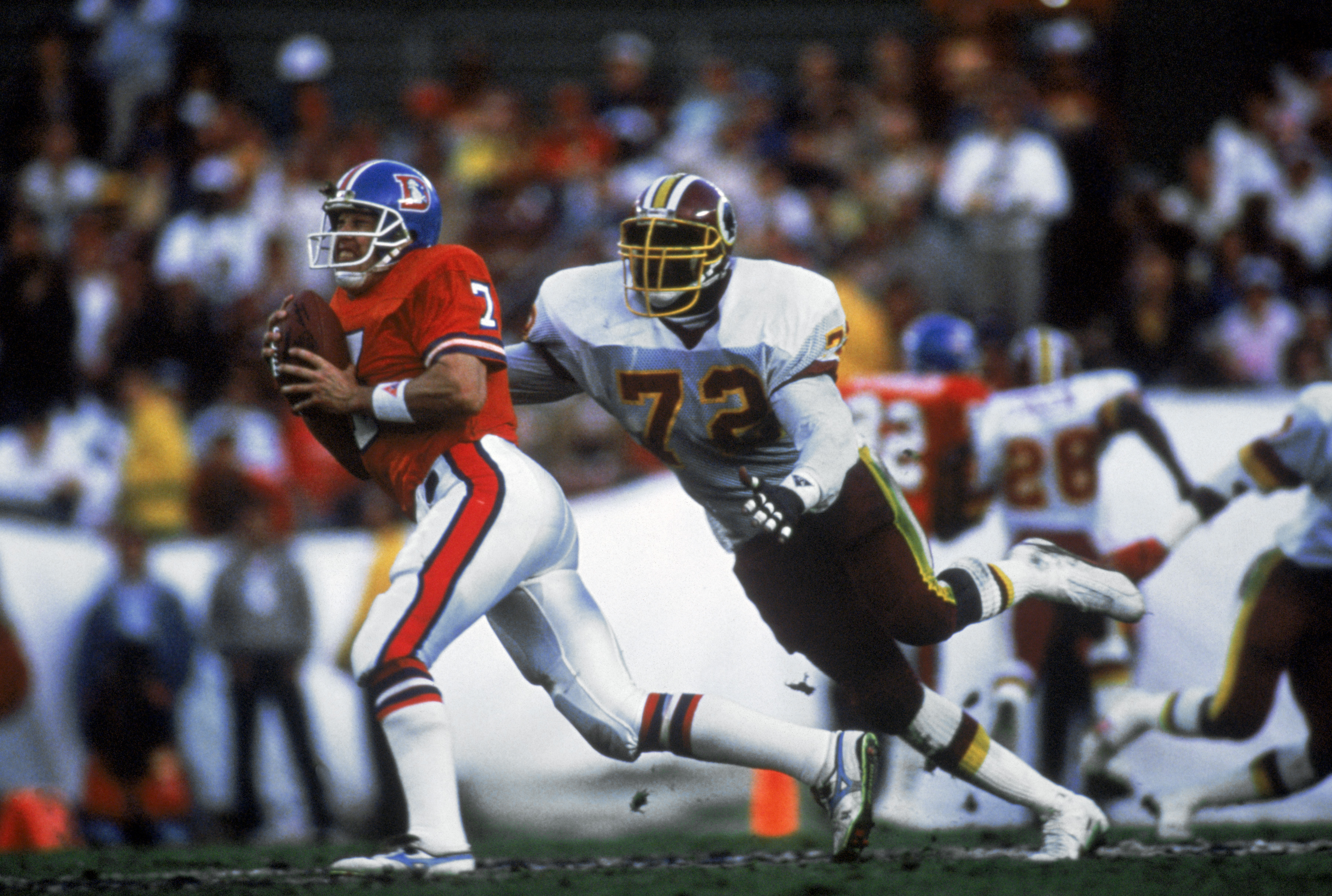 SAN DIEGO - JANUARY 31:  Quarterback John Elway #7 of the Denver Broncos tries to avoid an onrushing Dexter Manley #72 of the Washington Redskins during Superbowl XXII on January 31, 1988 at San Diego Jack Murphy Stadium in San Diego, California.  The Red