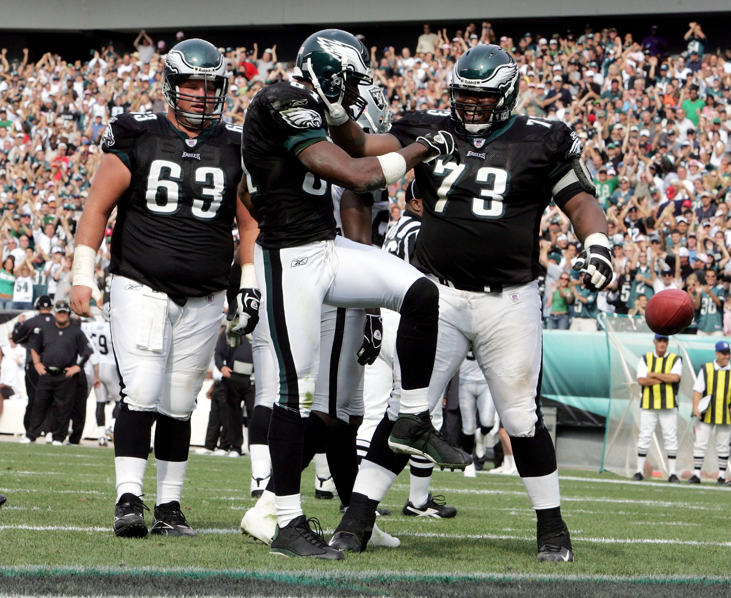 PHILADELPHIA - SEPTEMBER 25:  Wide receiver Terrell Owens #81 of the Philadelphia Eagles kicks the ball away as he celebrates his touchdown with teammates Hank Fraley #63 and Shawn Andrews #73 during the third quarter of their game against the Oakland Rai
