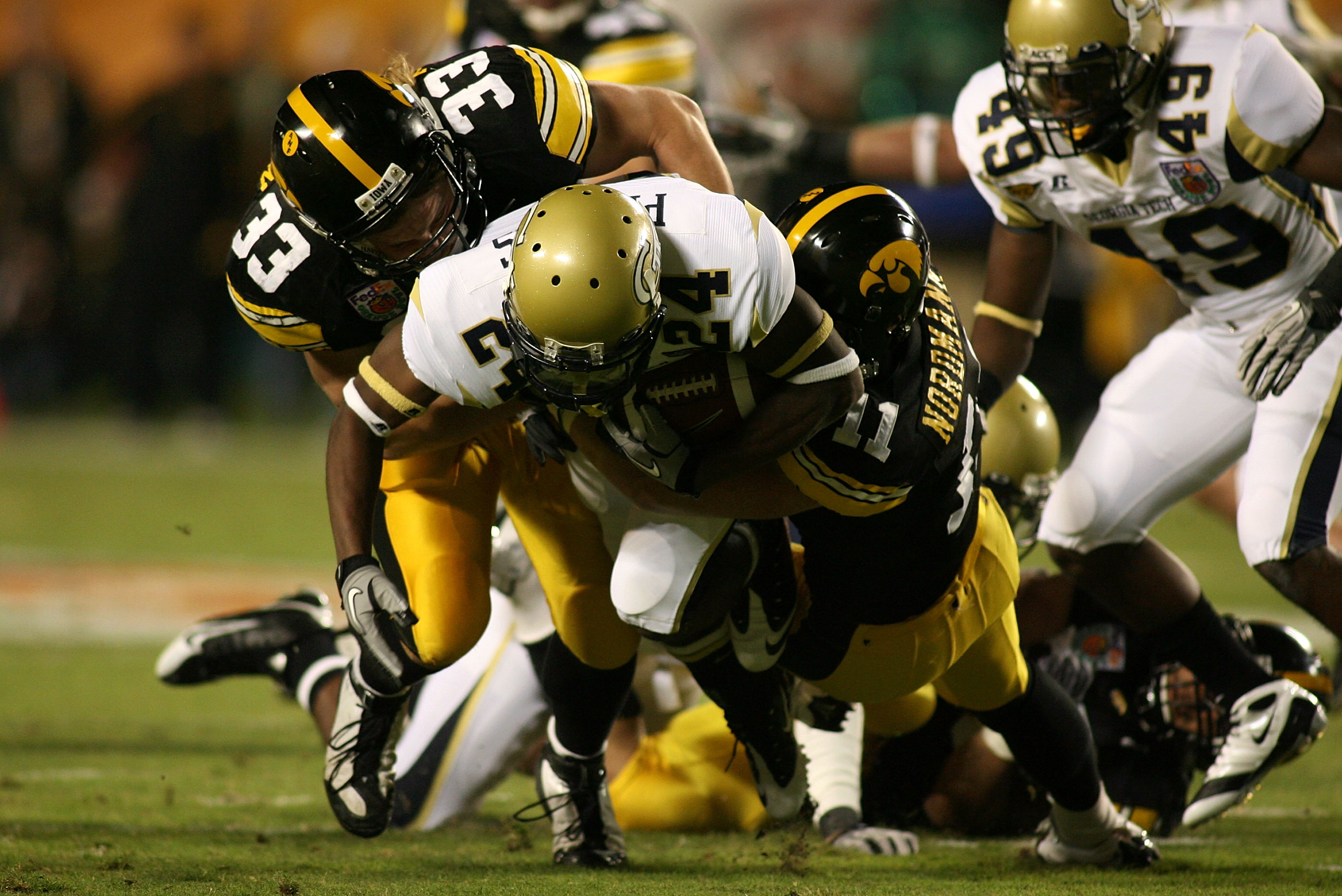 MIAMI GARDENS, FL - JANUARY 05:  Embry Peeples of the Georgia Tech Yellow Jackets is bought down by Jeff Tarpinian #33 and Don Nordmann #11 of the Iowa Hawkeyes during the FedEx Orange Bowl at Land Shark Stadium on January 5, 2010 in Miami Gardens, Florid