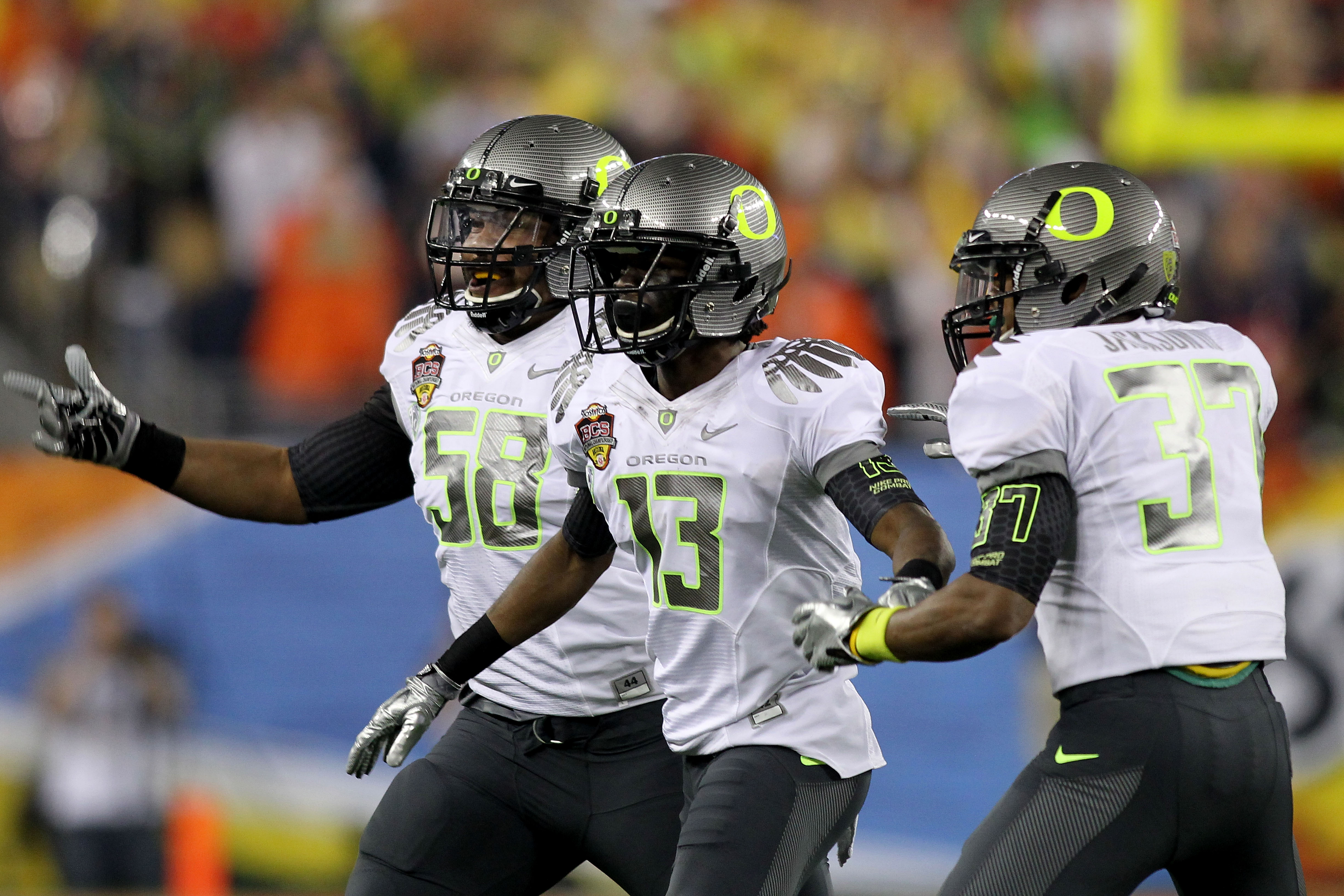 GLENDALE, AZ - JANUARY 10:  Cliff Harris #13 of the Oregon Ducks celebrates his first quarter interception with teammates Drew Howell #50 and Talmadge Jackson III #37 against the Auburn Tigers during the Tostitos BCS National Championship Game at Universi