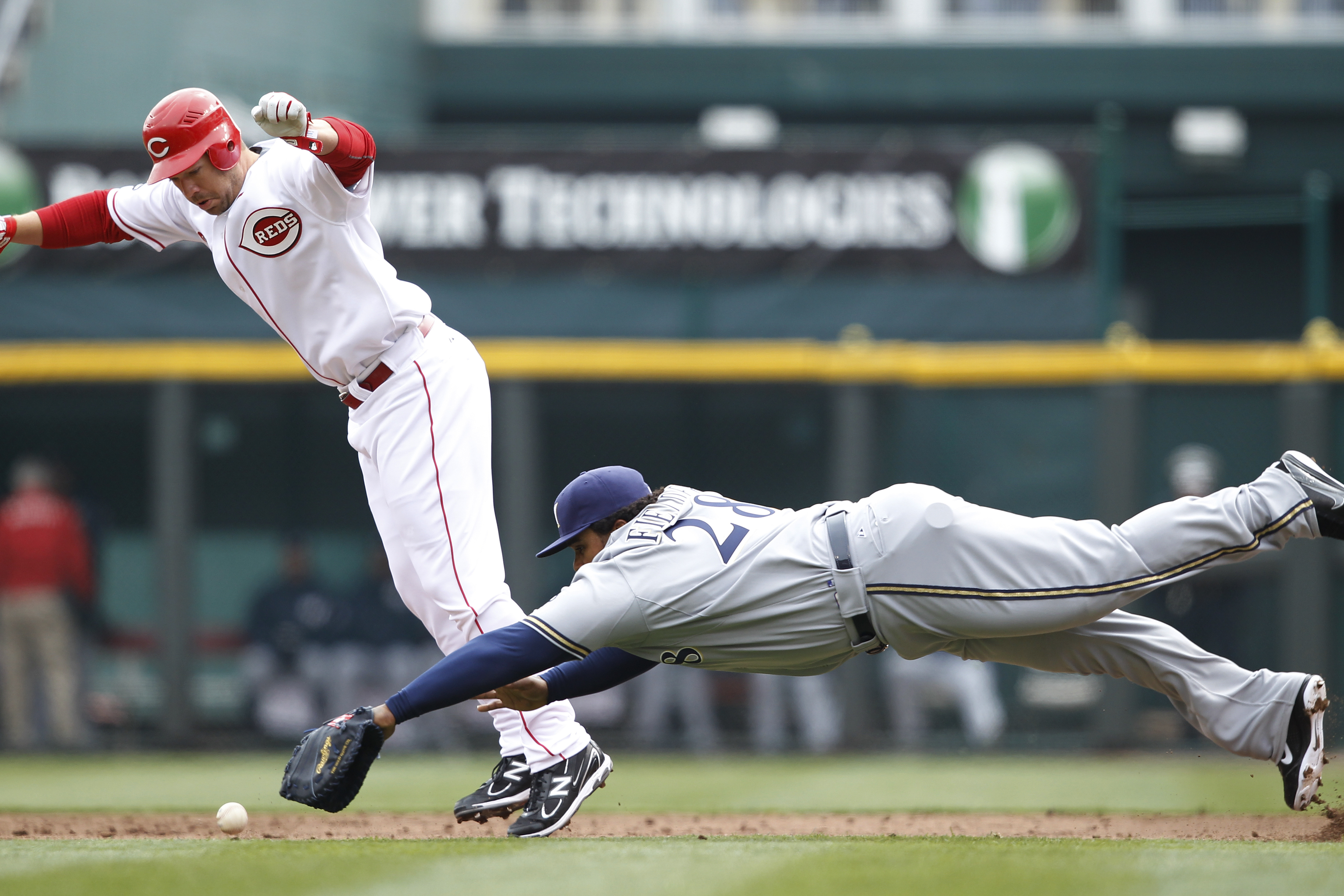 CINCINNATI, OH - MARCH 31: Scott Rolen #27 of the Cincinnati Reds tries to avoid Prince Fielder #28 of the Milwaukee Brewers on a ground ball during the opening day game at Great American Ballpark on March 31, 2011 in Cincinnati, Ohio. (Photo by Joe Robbi