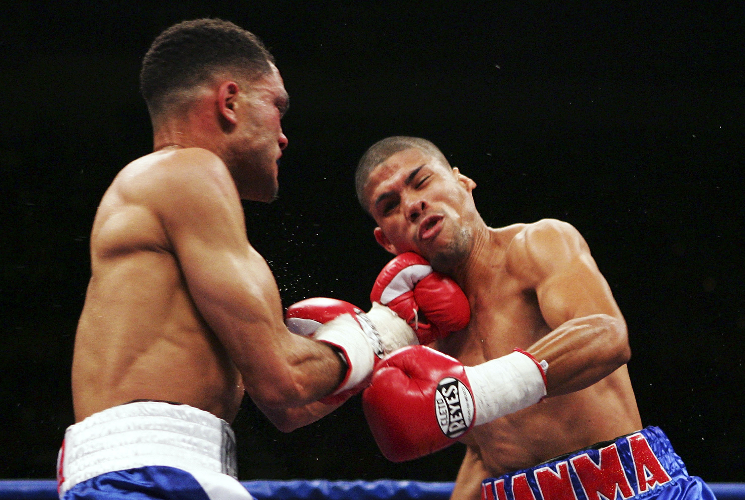 SAN JUAN, PUERTO RICO - MARCH 03:  Juan Manuel Lopez (R) receives a punch from Juan Brea during their fight on March 3, 2007 at the Roberto Clemente Coliseo in San Juan, Puerto Rico.  (Photo by Al Bello/Getty Images)