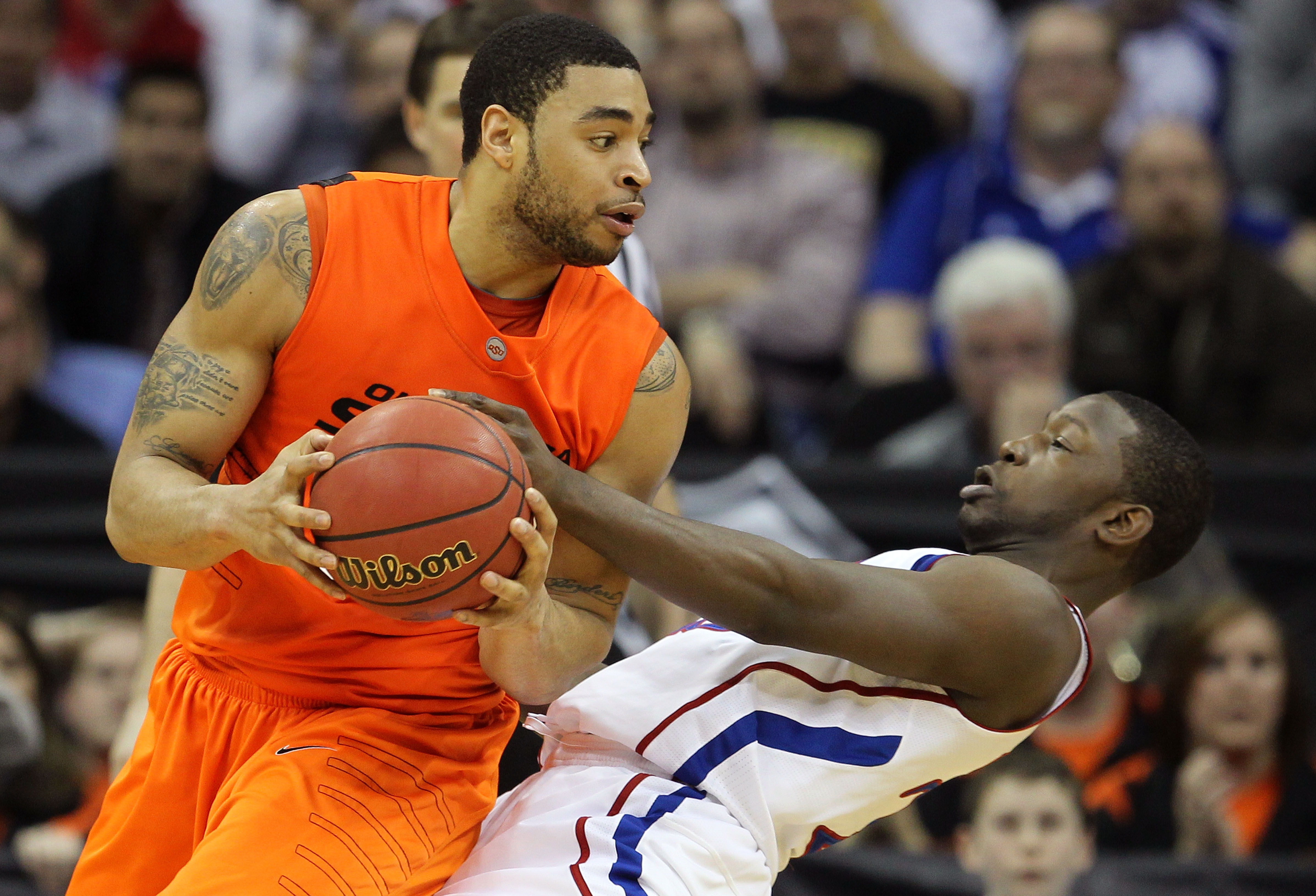 KANSAS CITY, MO - MARCH 10:  Marshall Moses #33 of the Oklahoma State Cowboys drives with the ball on Mario Little #23 of the Kansas Jayhawks during their quarterfinal game in the 2011 Phillips 66 Big 12 Men's Basketball Tournament at Sprint Center on Mar