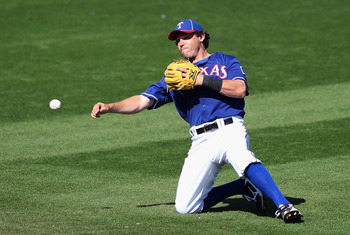 SURPRISE, AZ - MARCH 02:  Infielder Ian Kinsler #5 of the Texas Rangers fields a ground ball out against the Los Angeles Angels of Anaheim during the spring training game at Surprise Stadium on March 2, 2011 in Surprise, Arizona.  (Photo by Christian Pete
