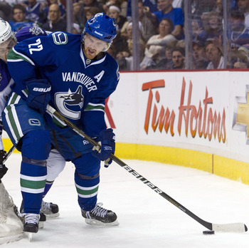 VANCOUVER, CANADA - MARCH 31: Daniel Sedin #22 of the Vancouver Canucks tries to fight off the check of Trevor Lewis #22 of the Los Angeles Kings during the second period in NHL action on March 31, 2011 at Rogers Arena in Vancouver, BC, Canada.  (Photo by