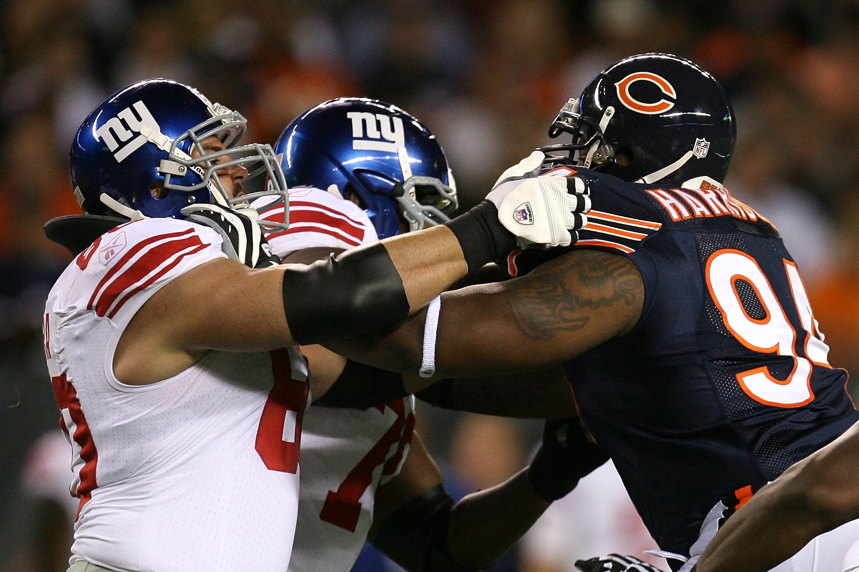CHICAGO - AUGUST 22: Shaun O'Hara #60 of the New York Giants blocks Marcus Harrison #94 of the Chicago Bears during a pre-season game on August 22, 2009 at Soldier Field in Chicago, Illinois. The Bears defeated the Giants 17-3. (Photo by Jonathan Daniel/G