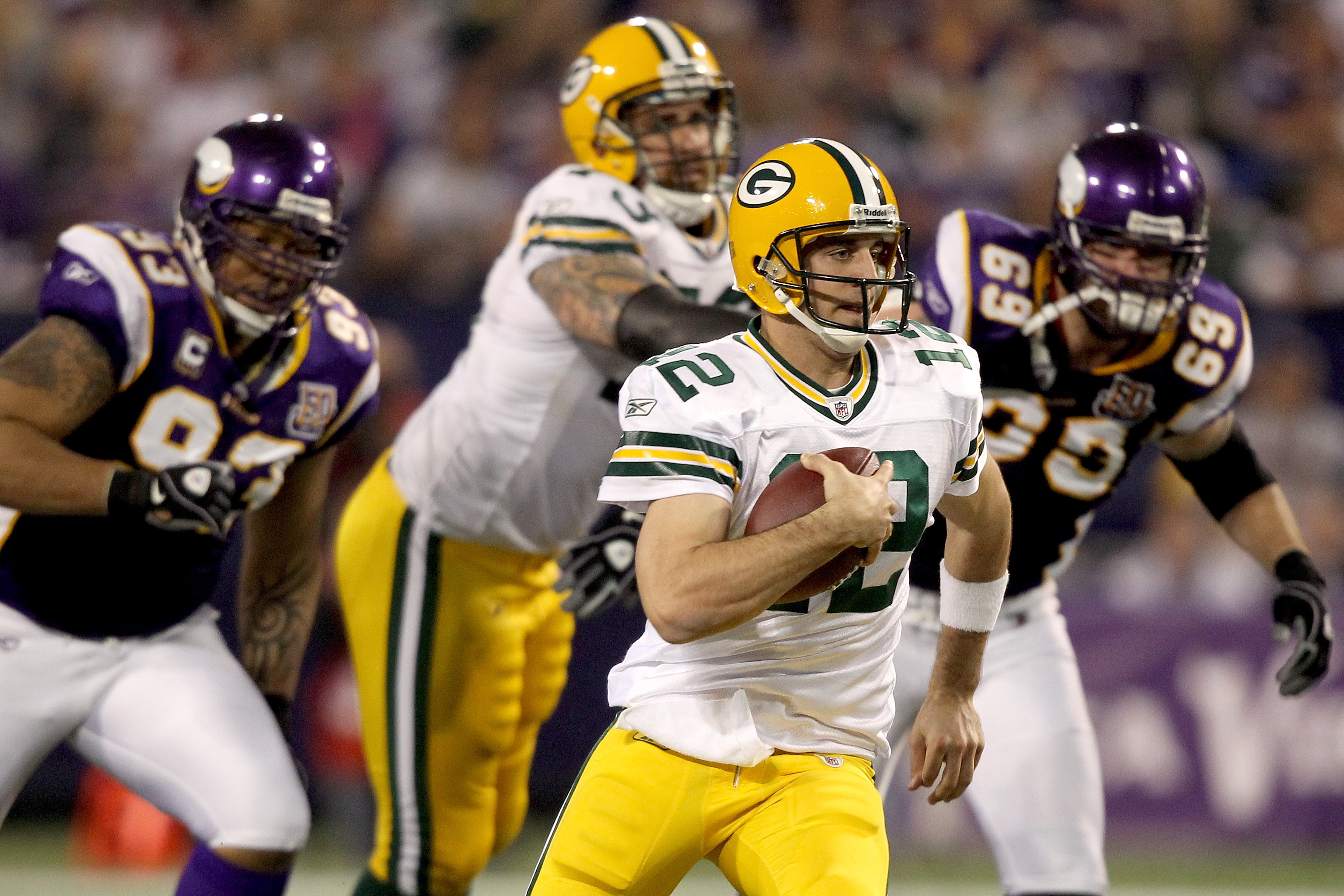 MINNEAPOLIS - NOVEMBER 21:  Quarterback Aaron Rodgers #12 of the Green Bay Packers is chased from the pocket by the Minnesota Vikings  at the Hubert H. Humphrey Metrodome on November 21, 2010 in Minneapolis, Minnesota.  (Photo by Matthew Stockman/Getty Im