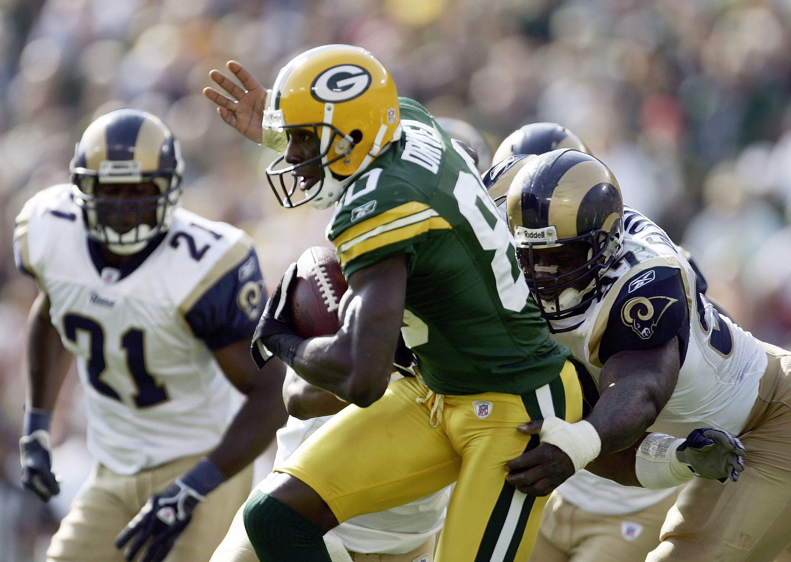 GREEN BAY, WI - OCTOBER 08:  Donald Driver #80 of the Green Bay Packers tries to break free from the tackle of La'Roi Glover #97 of the St. Louis Rams at Lambeau Field on October 8, 2006 in Green Bay, Wisconsin. The Rams won 23-20.  (Photo by Harry How/Ge