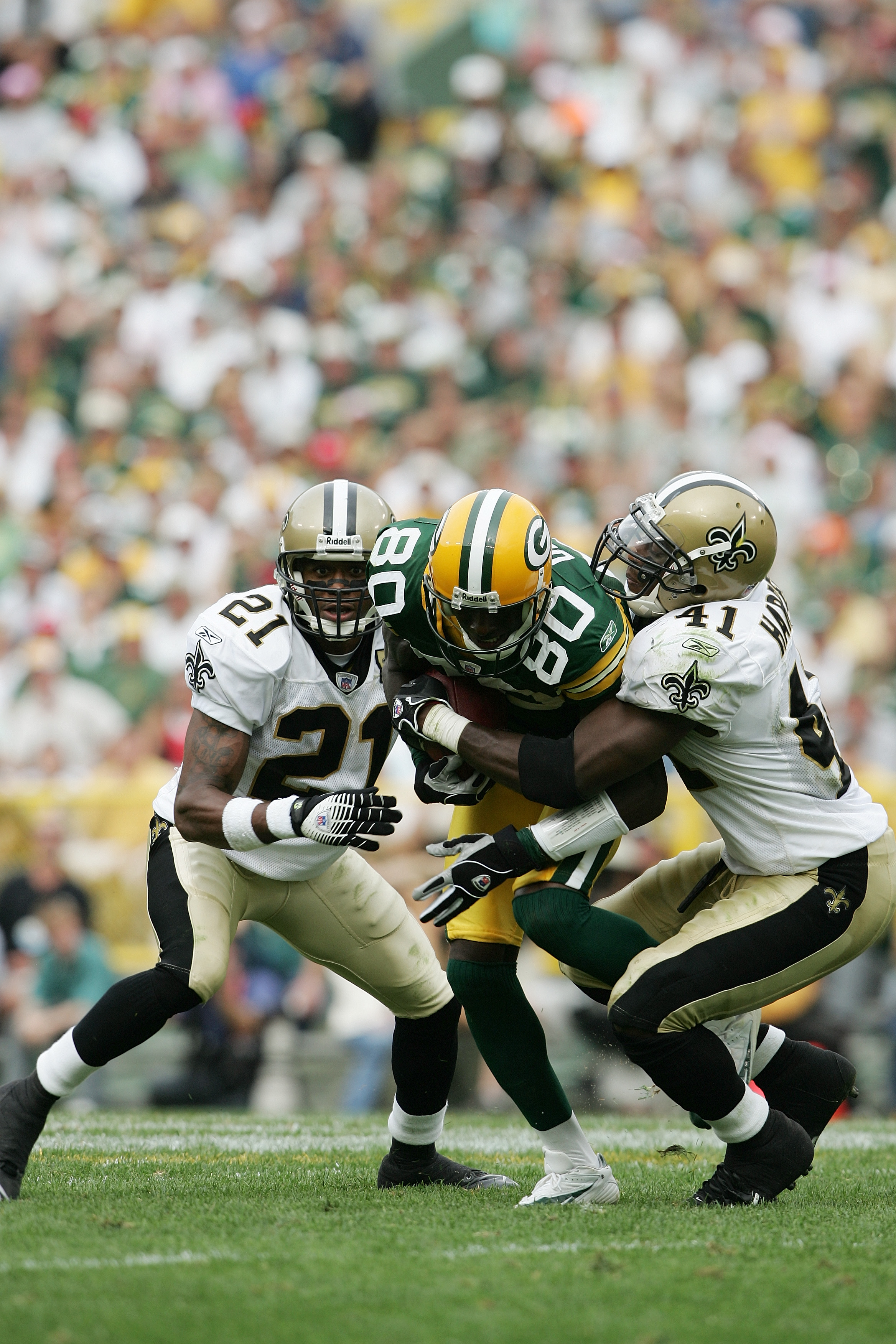 GREEN BAY, WI - SEPTEMBER 17:  Wide receiver Donald Driver #80 of the Green Bay Packers fights off the tackle attempt of cornerback Jason Craft #21 and safety Roman Harper #41 of the New Orleans Saints on September 17, 2006 at Lambeau Field in Green Bay,