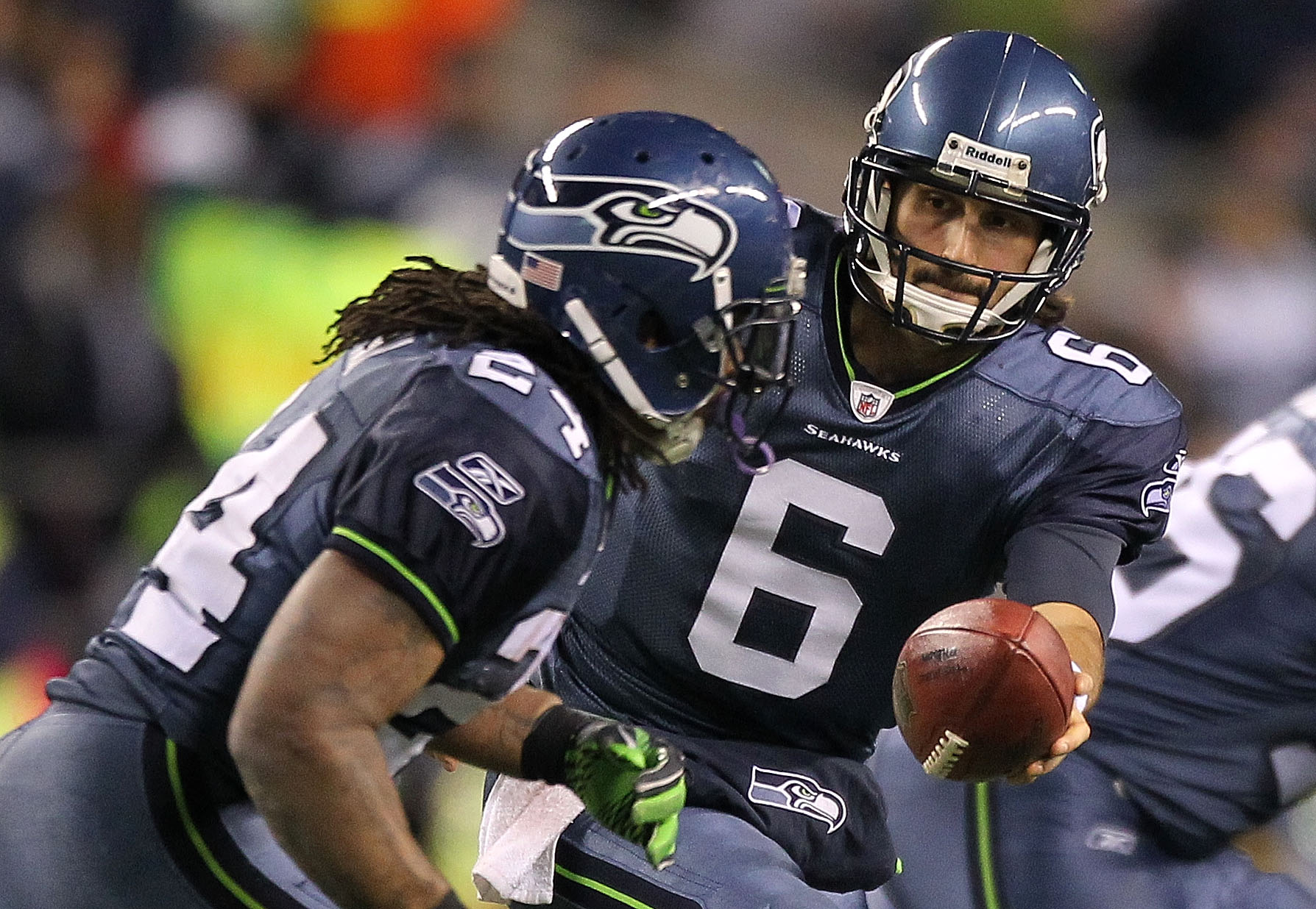 SEATTLE, WA - JANUARY 02:  Quarterback Charlie Whitehurst #6 of the Seattle Seahawks hands the ball off to running back Marshawn Lynch #24 during their game against the St. Louis Rams at Qwest Field on January 2, 2011 in Seattle, Washington.  (Photo by Ot