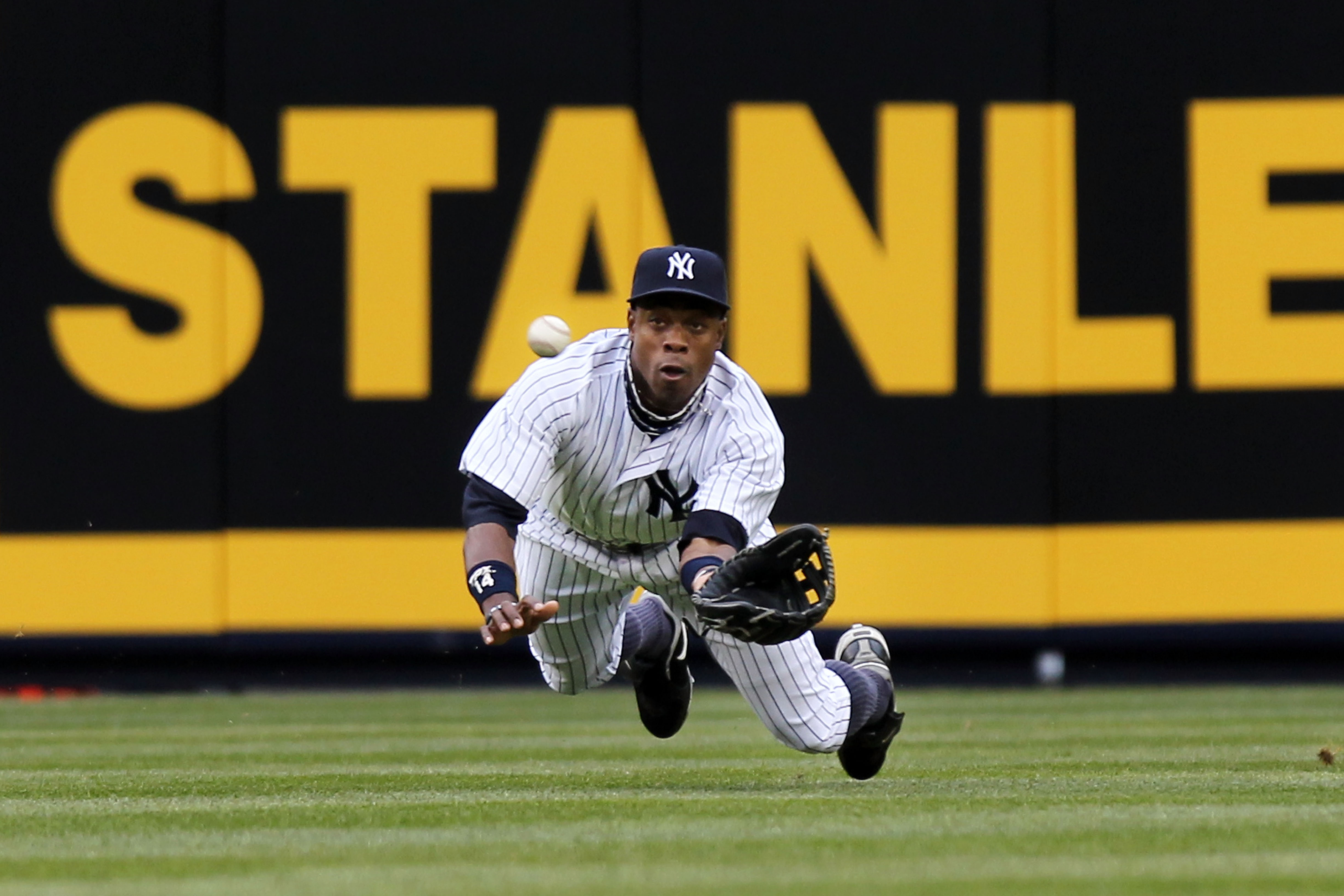 NEW YORK, NY - MARCH 31:  Curtis Granderson #14 of the New York Yankees dives to catch the ball for an out in the first inning against the Detroit Tigers on Opening Day at Yankee Stadium on March 31, 2011 in the Bronx borough of New York City. (Photo by N