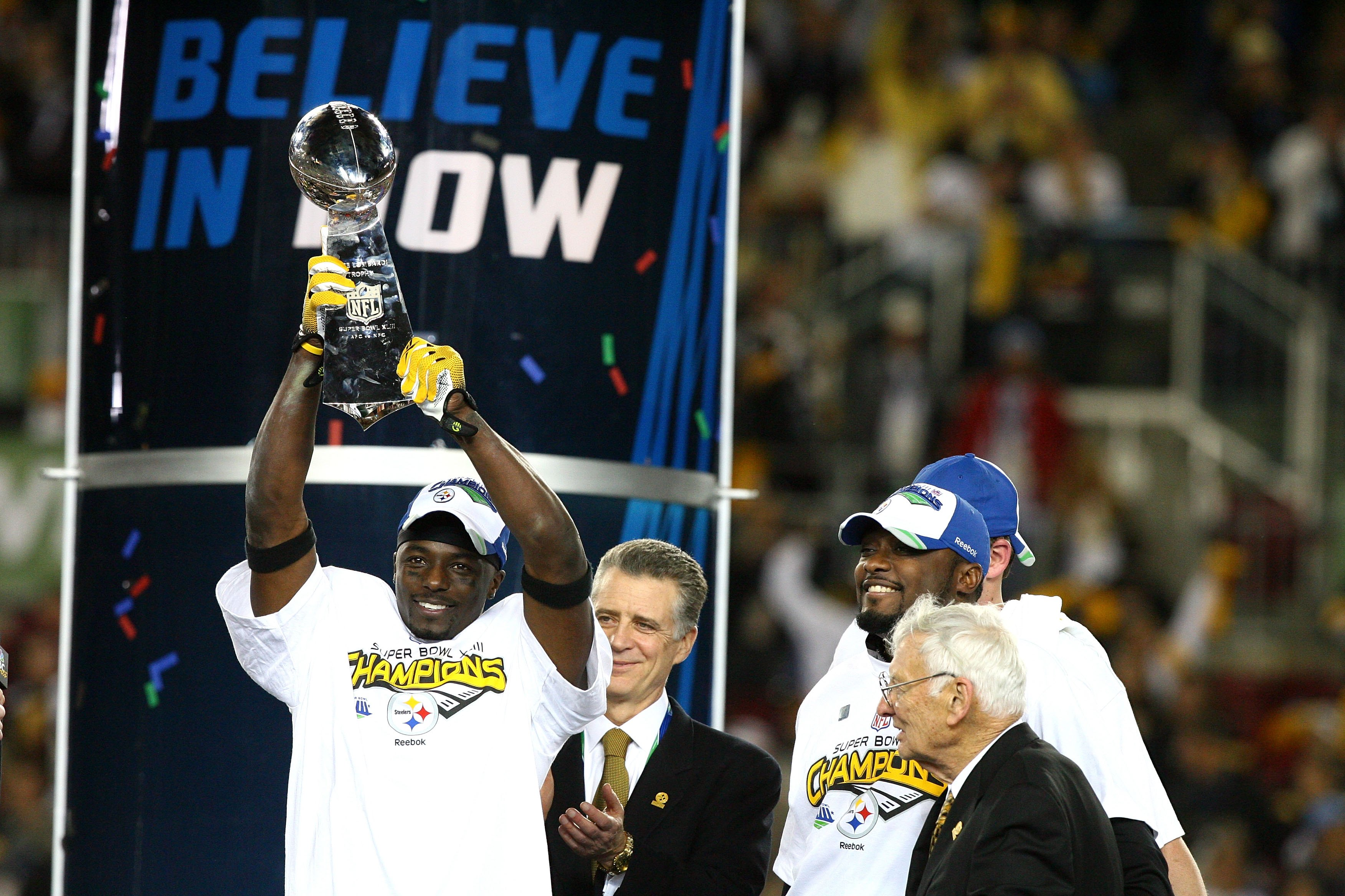 TAMPA, FL - FEBRUARY 01:  Santonio Holmes #10 of of the Pittsburgh Steelers celebrates with the Vince Lombardi Trophy as team owner Dan Rooney and head coach Mike Tomlin looks on after the Steelers won 27-23 against the Arizona Cardinals during Super Bowl