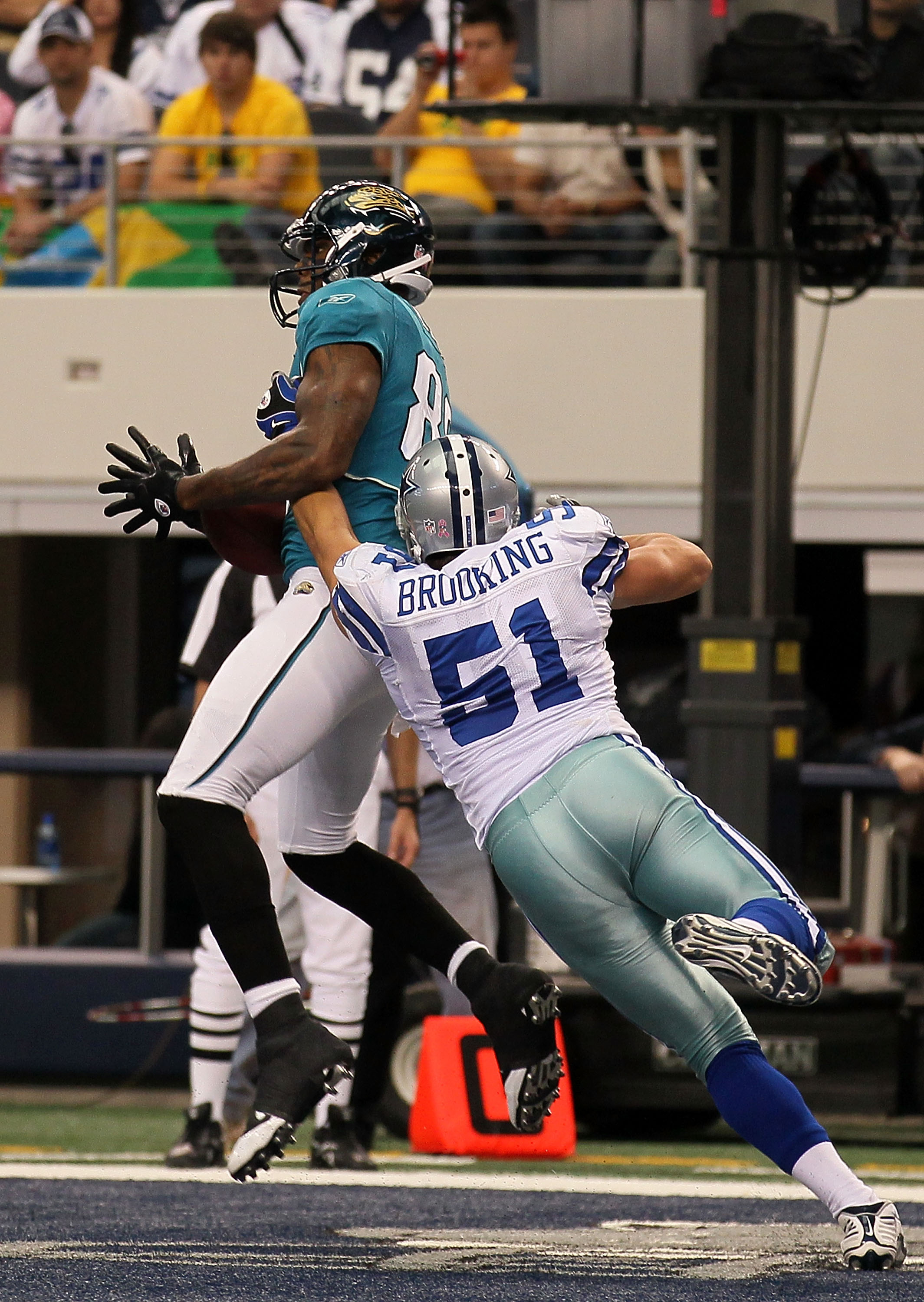 ARLINGTON, TX - OCTOBER 31:  Marcedes Lewis #89 of the Jacksonville Jaguars catches a 9-yard touchdown reception in the third quarter against Keith Brooking #51 of the Dallas Cowboys at Cowboys Stadium on October 31, 2010 in Arlington, Texas.  (Photo by S
