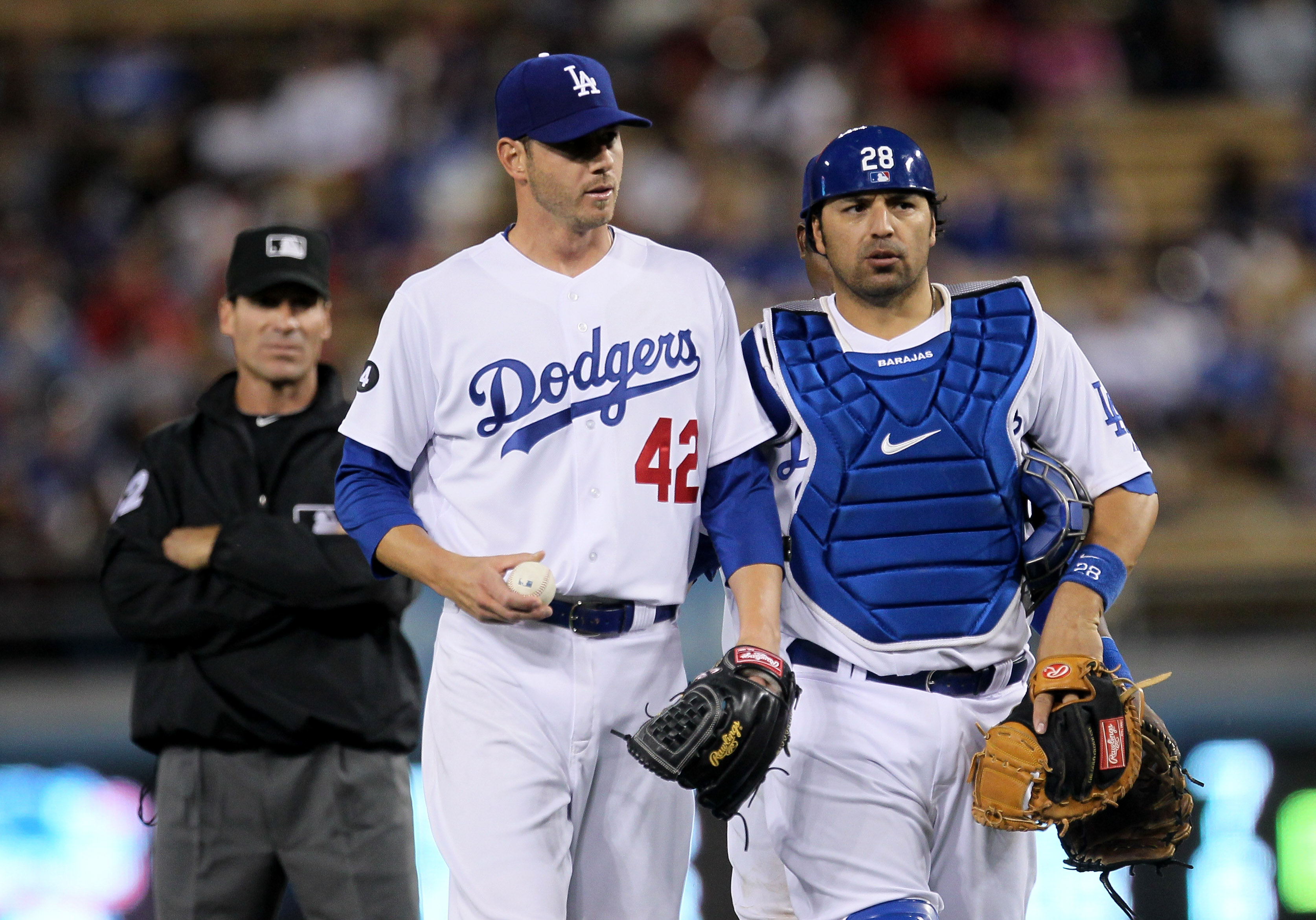 LOS ANGELES - APRIL 15:   Pitcher Jon Garland #21 of the Los Angeles Dodgers is walked back to the mound by catcher Rod Barajas #28 after arguing over a run scoring balk call by umpire Angel Hernandez (L) in the second inning against the St. Louis Cardina