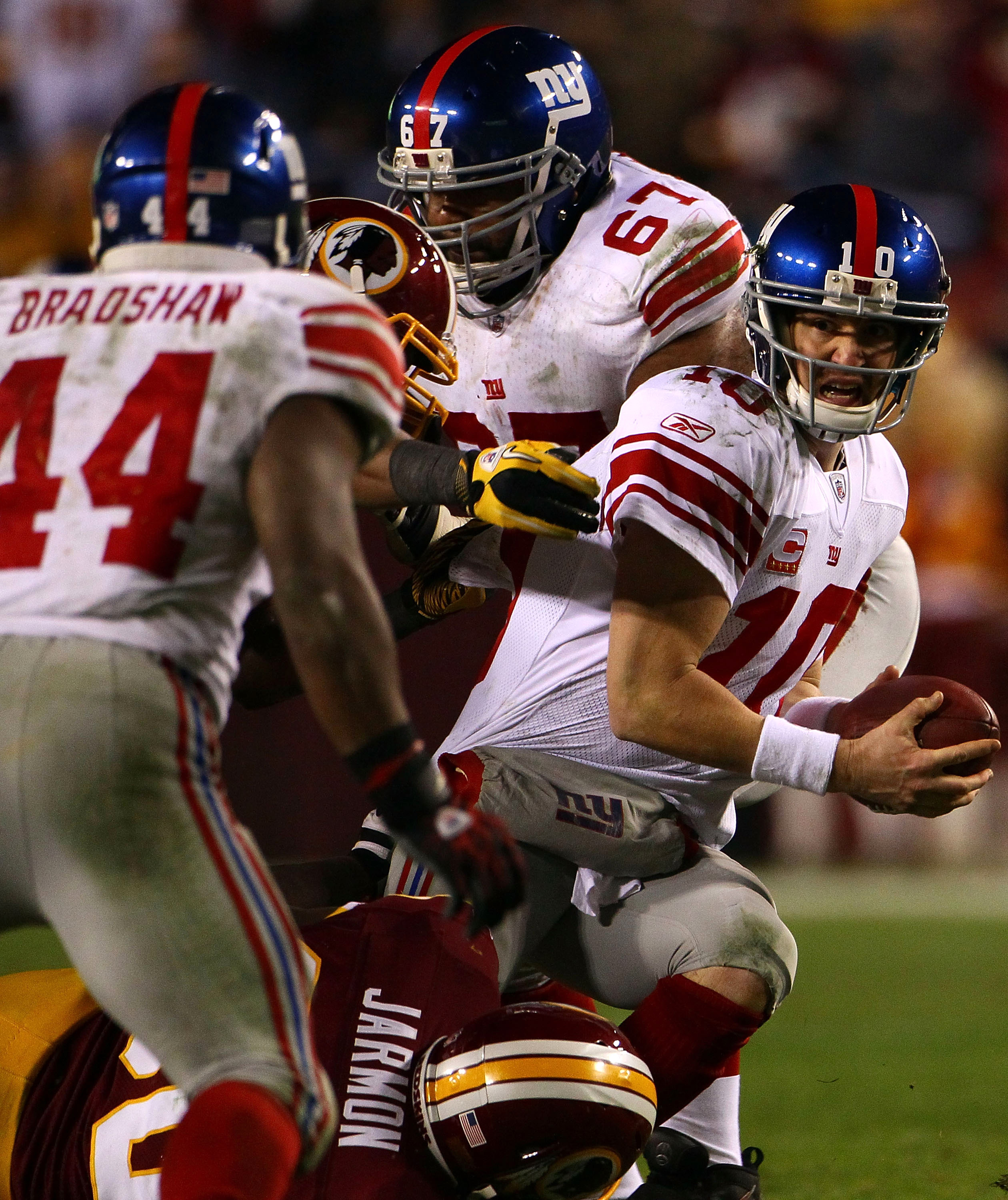 LANDOVER, MD - JANUARY 02:  Quarterback Eli Manning #10 of the New York Giants looks to Ahmad Bradshaw to lateral the ball while being pressured by the Washington Redskins defense during their game at FedEx Field on January 2, 2011 in Landover, Maryland.