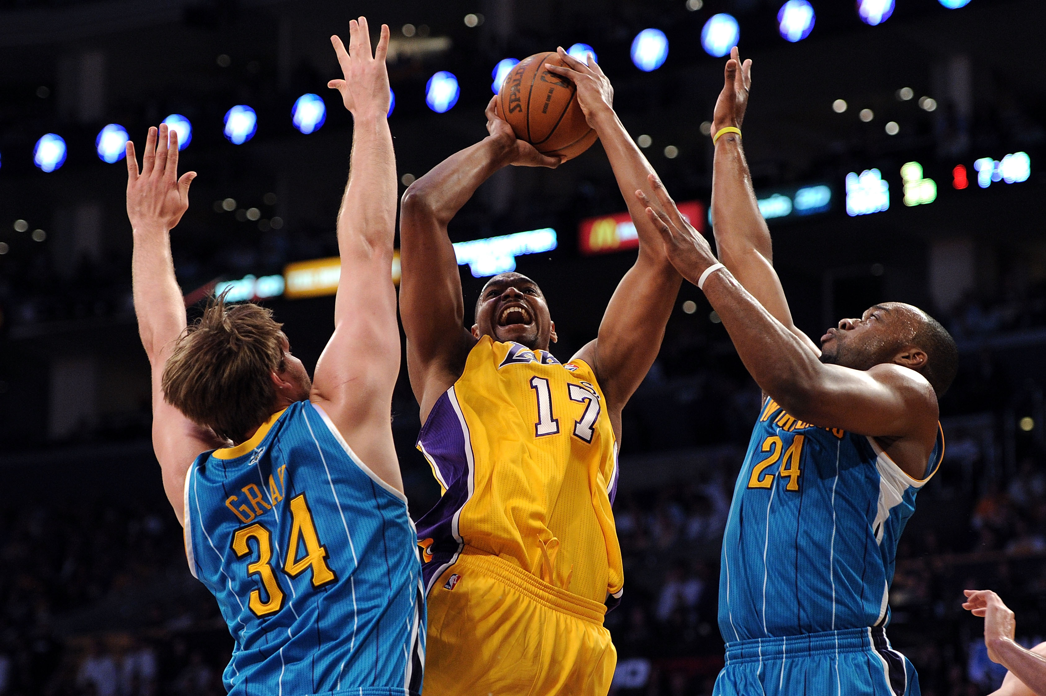 LOS ANGELES, CA - APRIL 20:  Andrew Bynum #17 of the Los Angeles Lakers shoots over Aaron Gray #34 and Carl Landry #24 of the New Orleans Hornets in the first quarter in Game Two of the Western Conference Quarterfinals in the 2011 NBA Playoffs on April 20