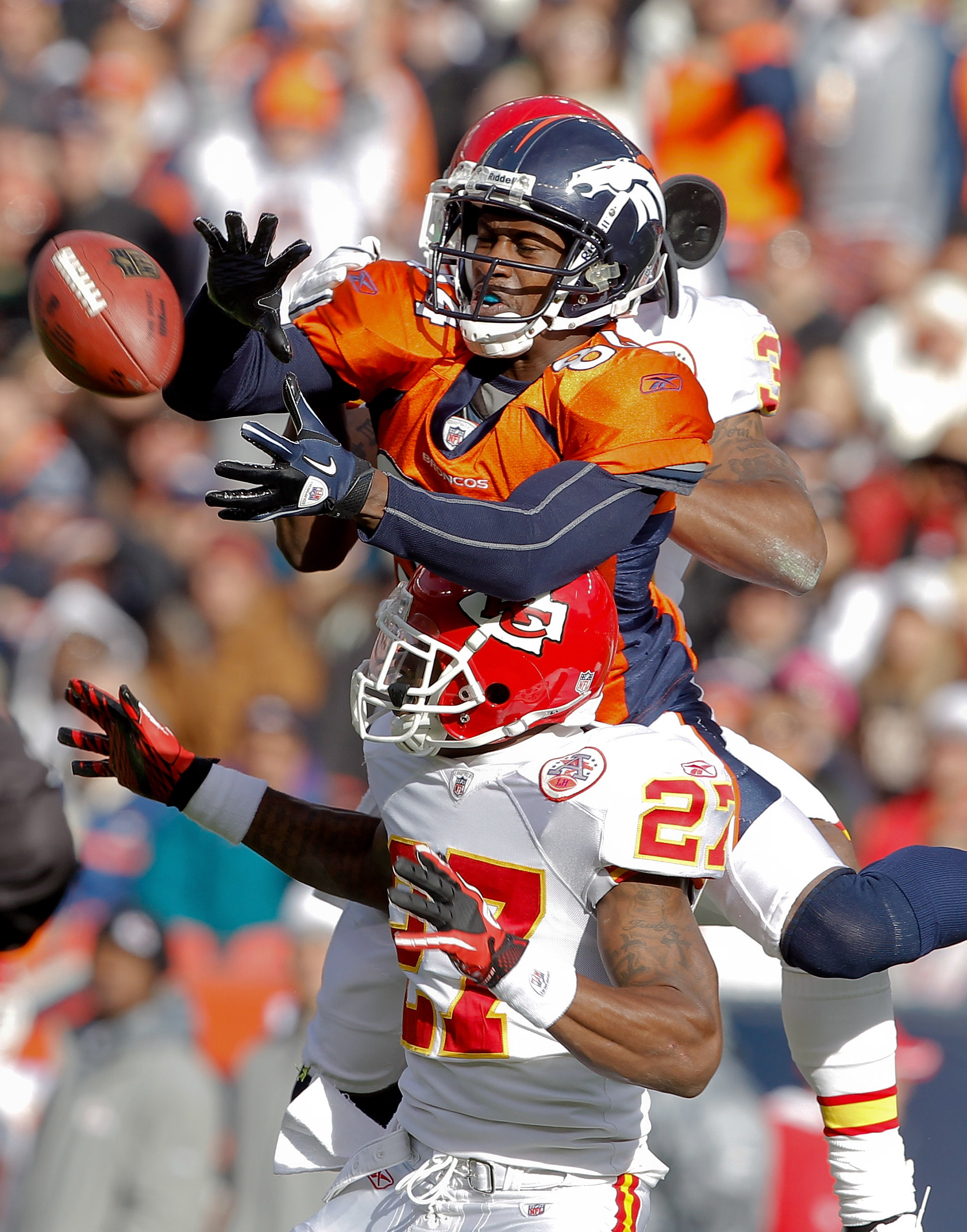 DENVER - NOVEMBER 14:  Wide receiver Brandon Lloyd #84 of the Denver Broncos makes a reception for a first down against cornerback Donald Washington #27 of the Kansas City Chiefs and teammate cornerback Brandon Carr #39 in the first quarter at INVESCO Fie