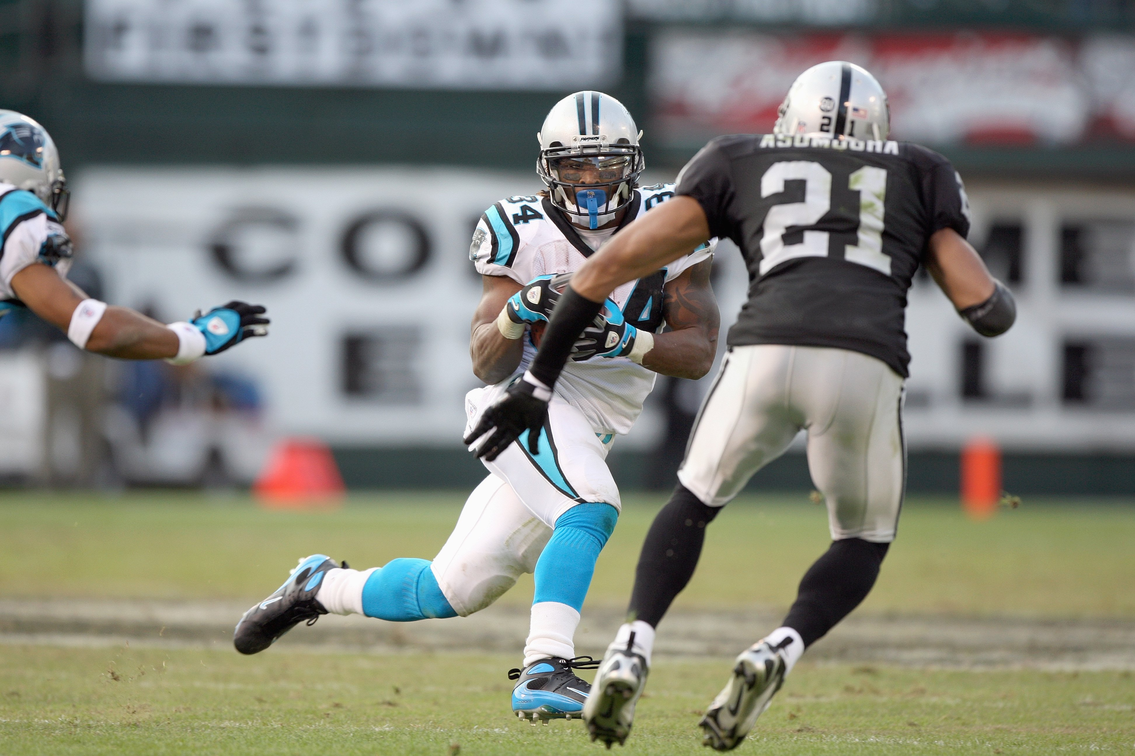 OAKLAND - NOVEMBER 9:  DeAngelo Williams #34 of the Carolina Panthers carries the ball against Nnamdi Asomugha #21 of the Oakland Raiders at the Oakland-Alameda County Coliseum on November 9, 2008 in Oakland, California. (Photo by: Jed Jacobsohn/Getty Ima