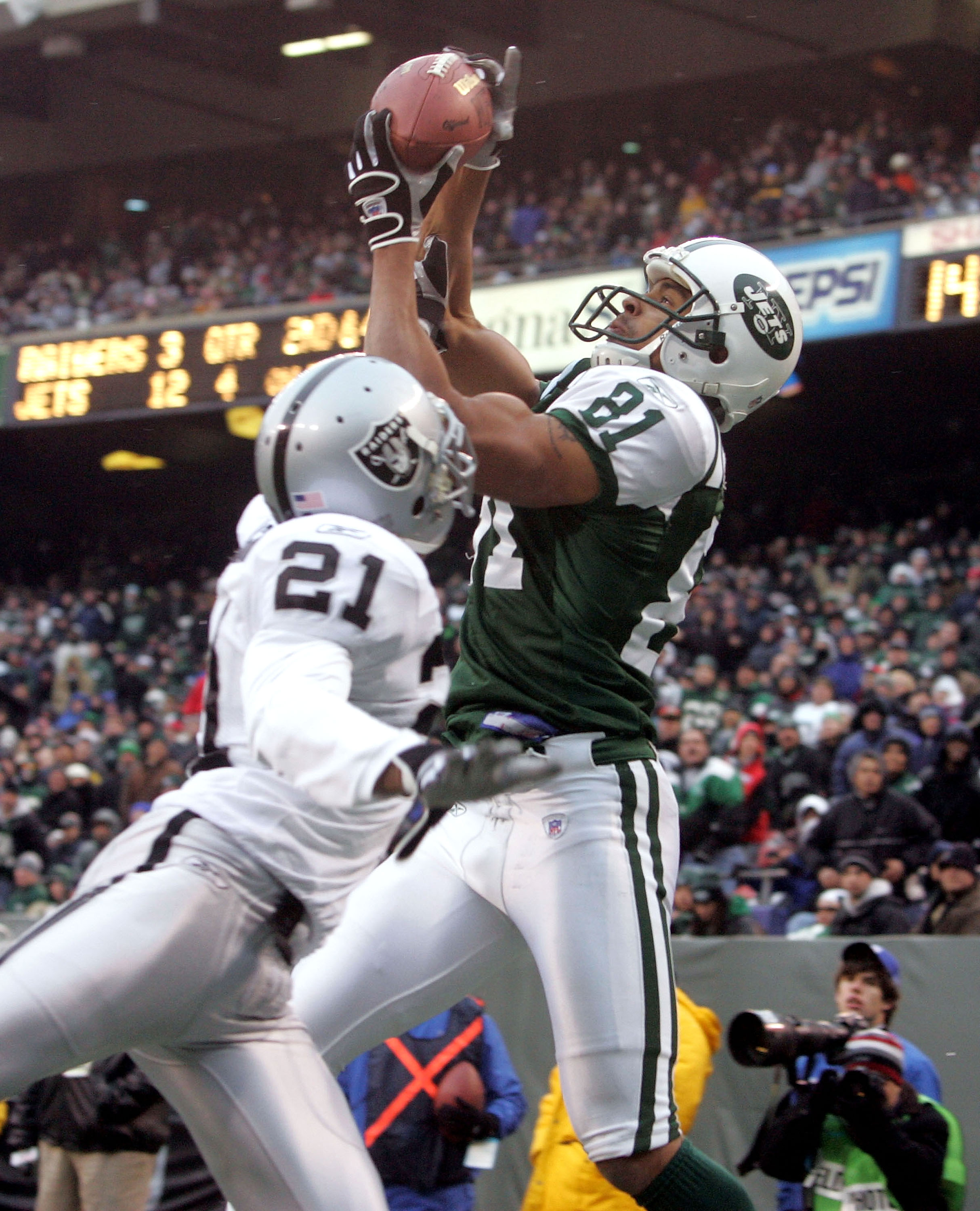 EAST RUTHERFORD, NJ - DECEMBER 11:  Wide receiver Justin McCareins #81 of the New York Jets catches a touchdown pass in the fourth quarter against cornerback Nnamdi Asomugha #21 of the Oakland Raiders on December 11, 2005 at Giants Stadium in East Rutherf